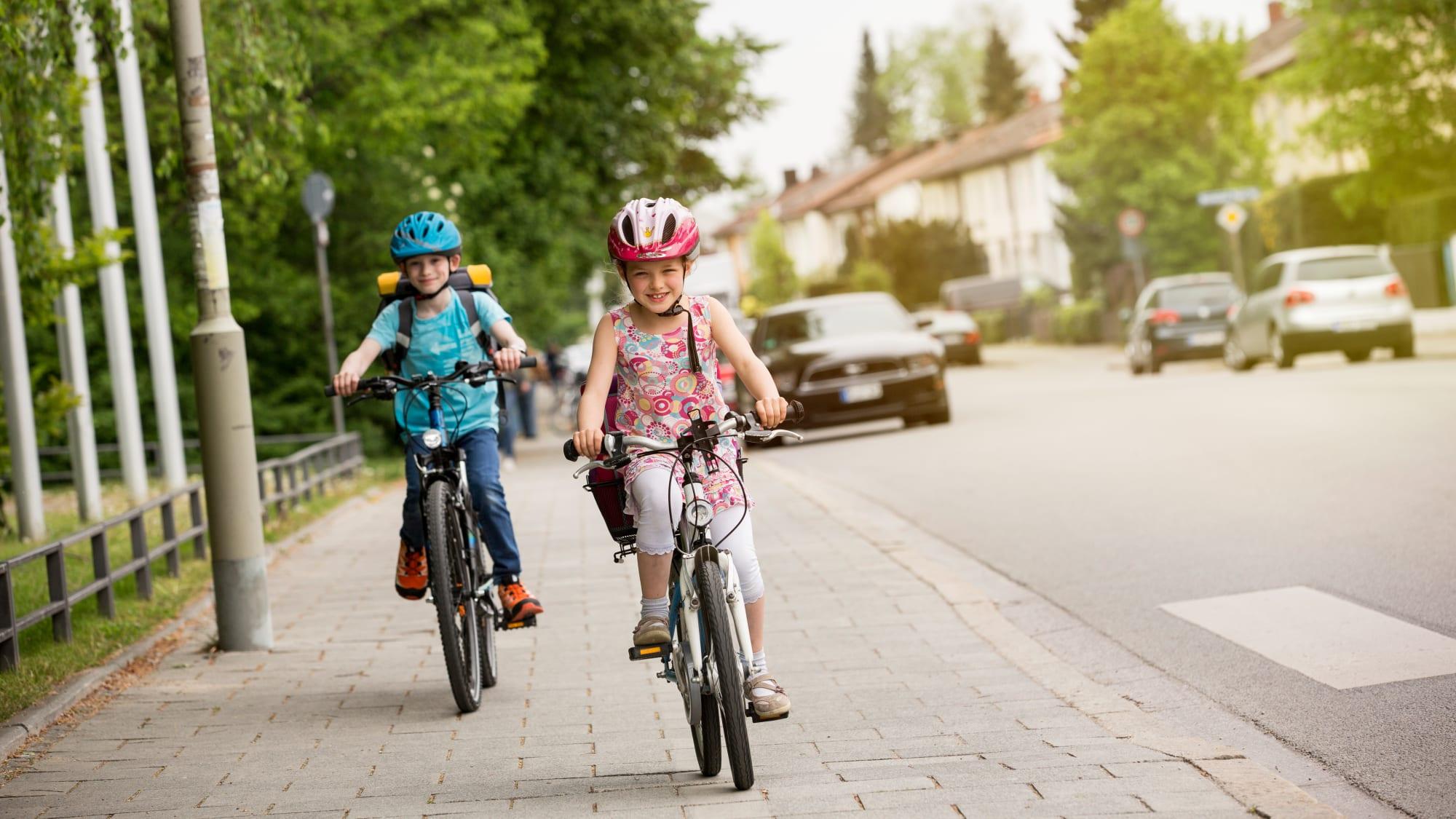 Kinder fahren mit Rad und Fahrradhelm auf dem Gehweg von derSchule nach Hause