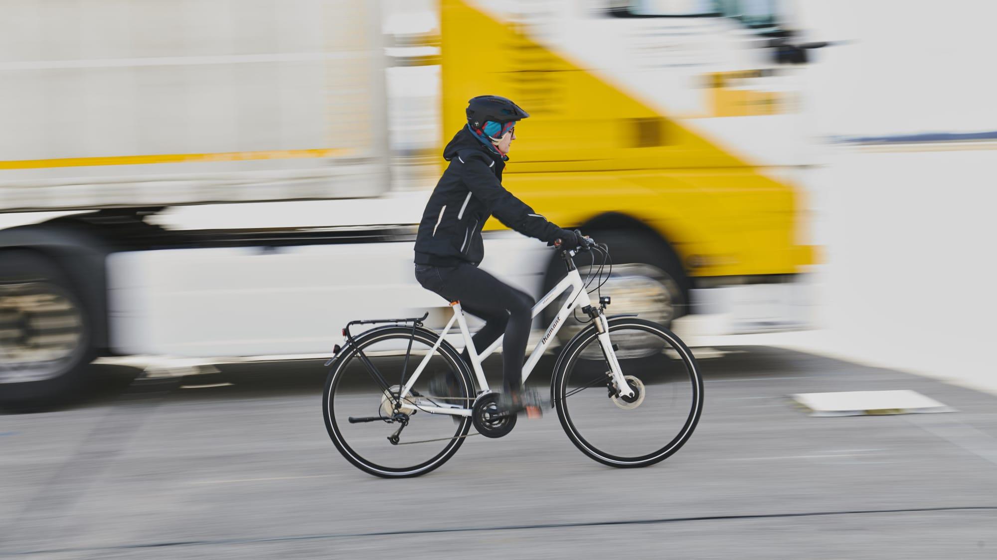 Fahrradfahrerin fährt neben LKW