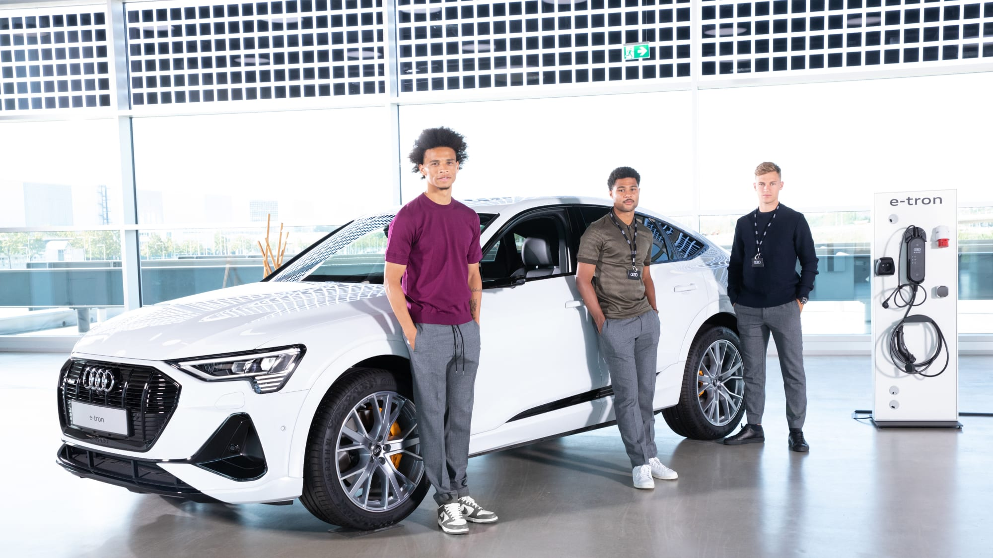 Leroy Sané, Serge Gnabry, Joshua Kimmich stehen vor einem Audi E-Tron