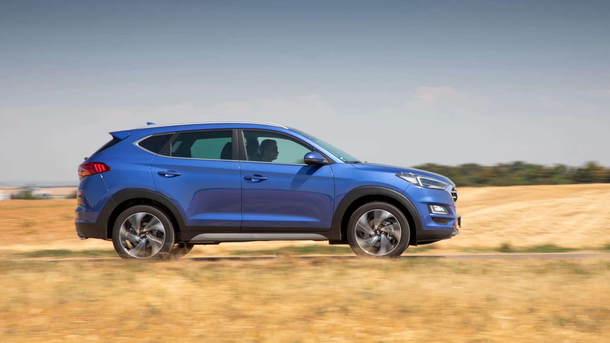 Blauer Hyundai Tucson faehrt durch Gelaende