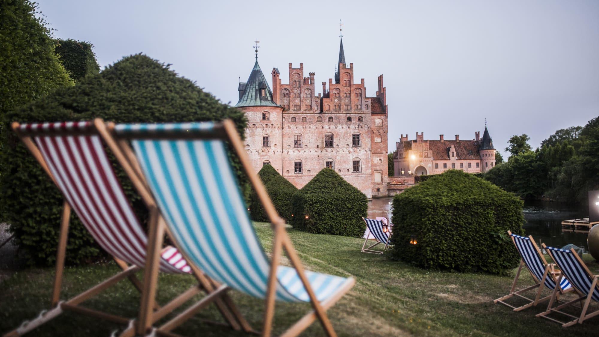 Zwei Liegestühle stehen auf einer Wiese und im Hintergrund sieht man das Schloss Egeskov