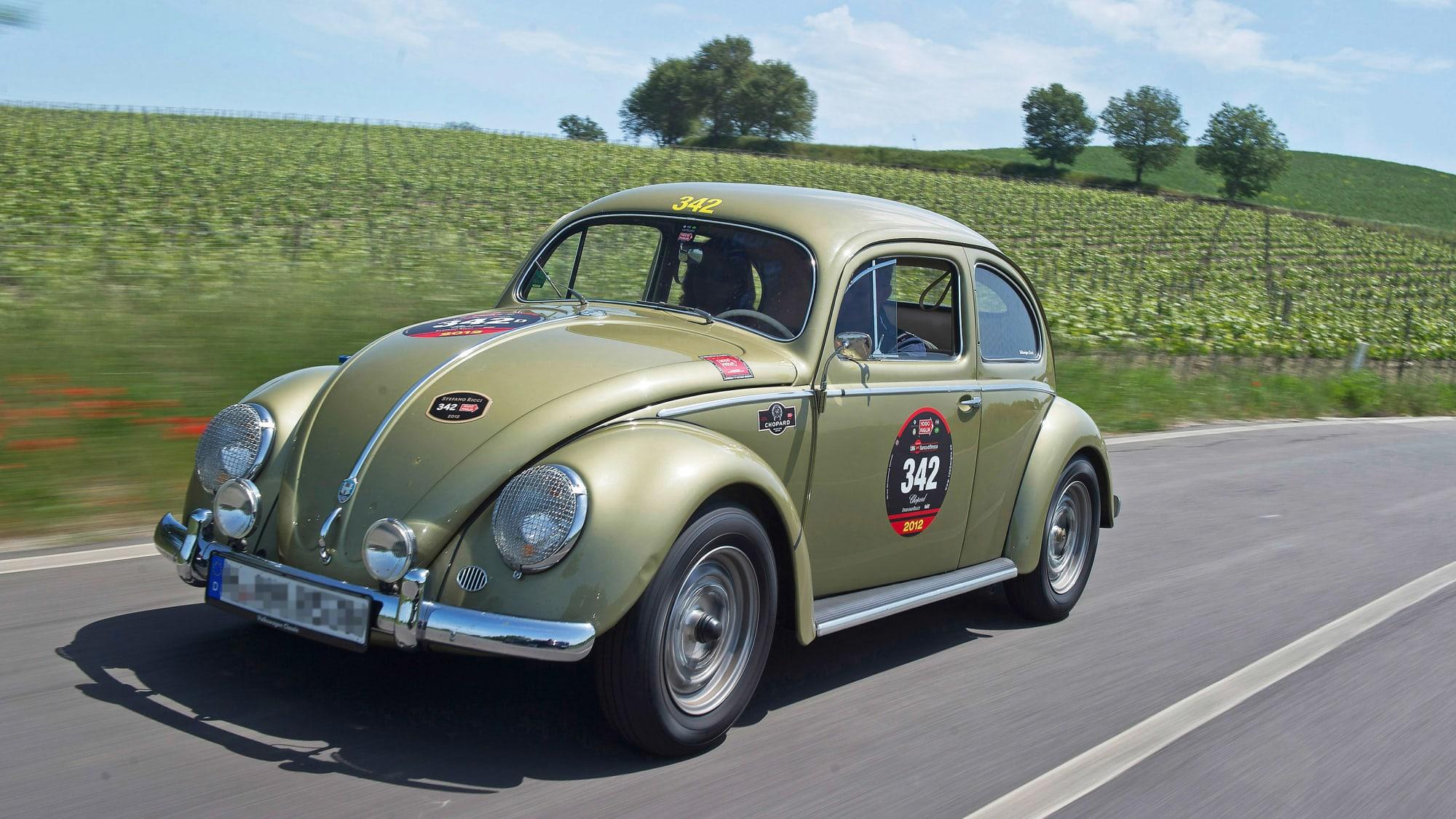 Grüner VW Käfer fährt auf einer Straße