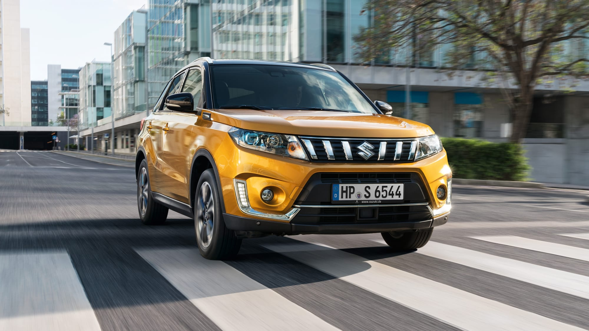 goldener Suzuki Vitara faehrt auf Strasse