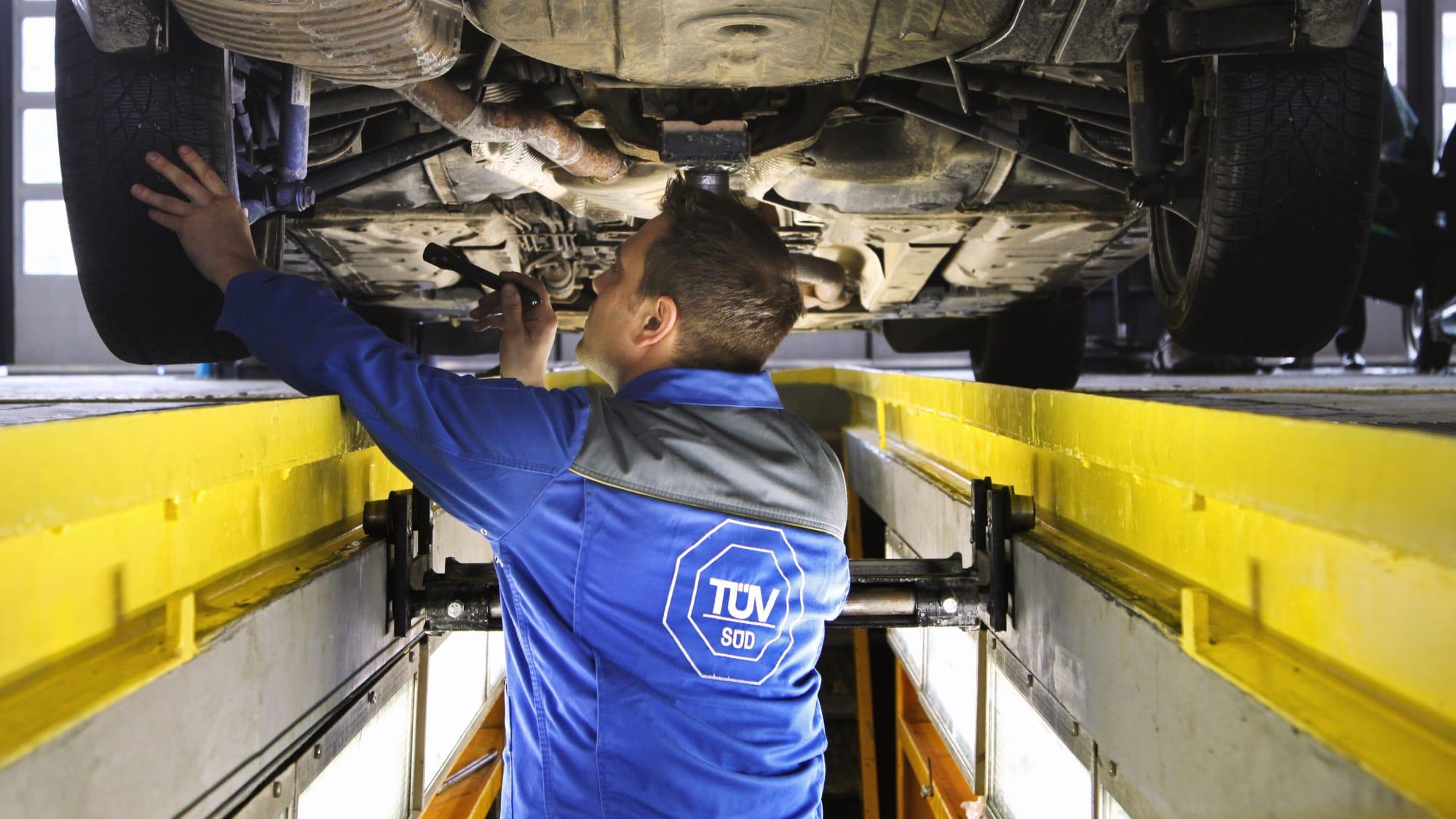TÜV-Mitarbeiter begutachtet Auto von unten