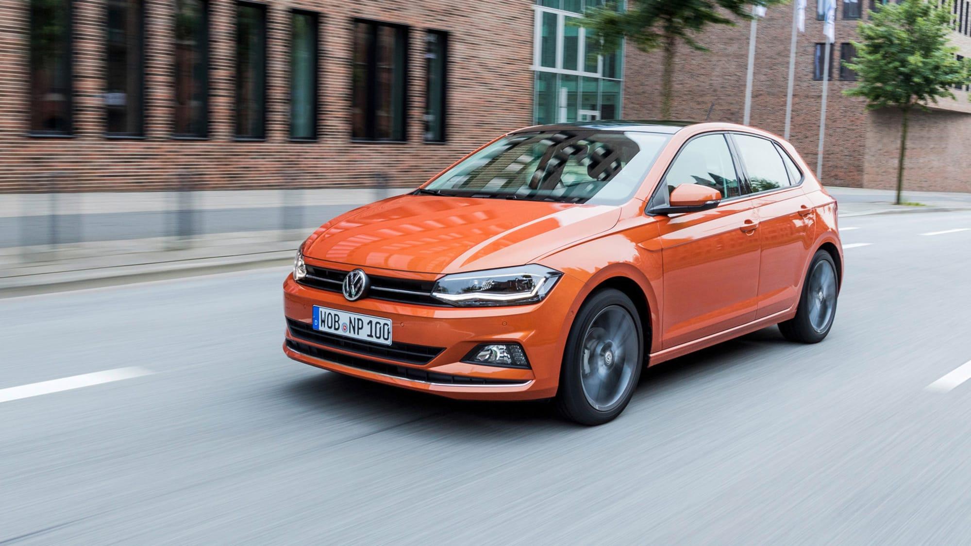 orangener VW Polo faehrt durch Stadt