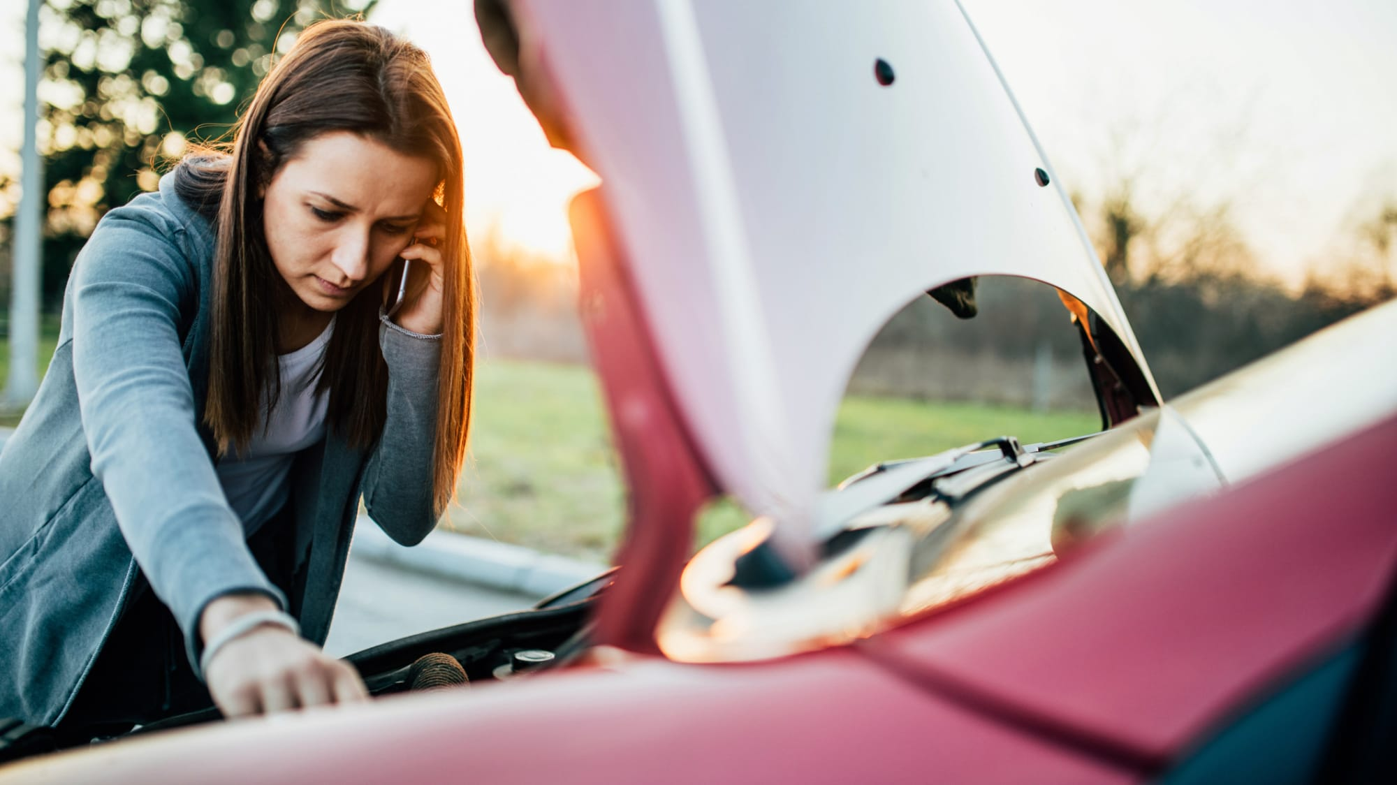 Junge Frau telefoniert beim Blick in die Motorhaube weil ihr Auto nicht anspringt