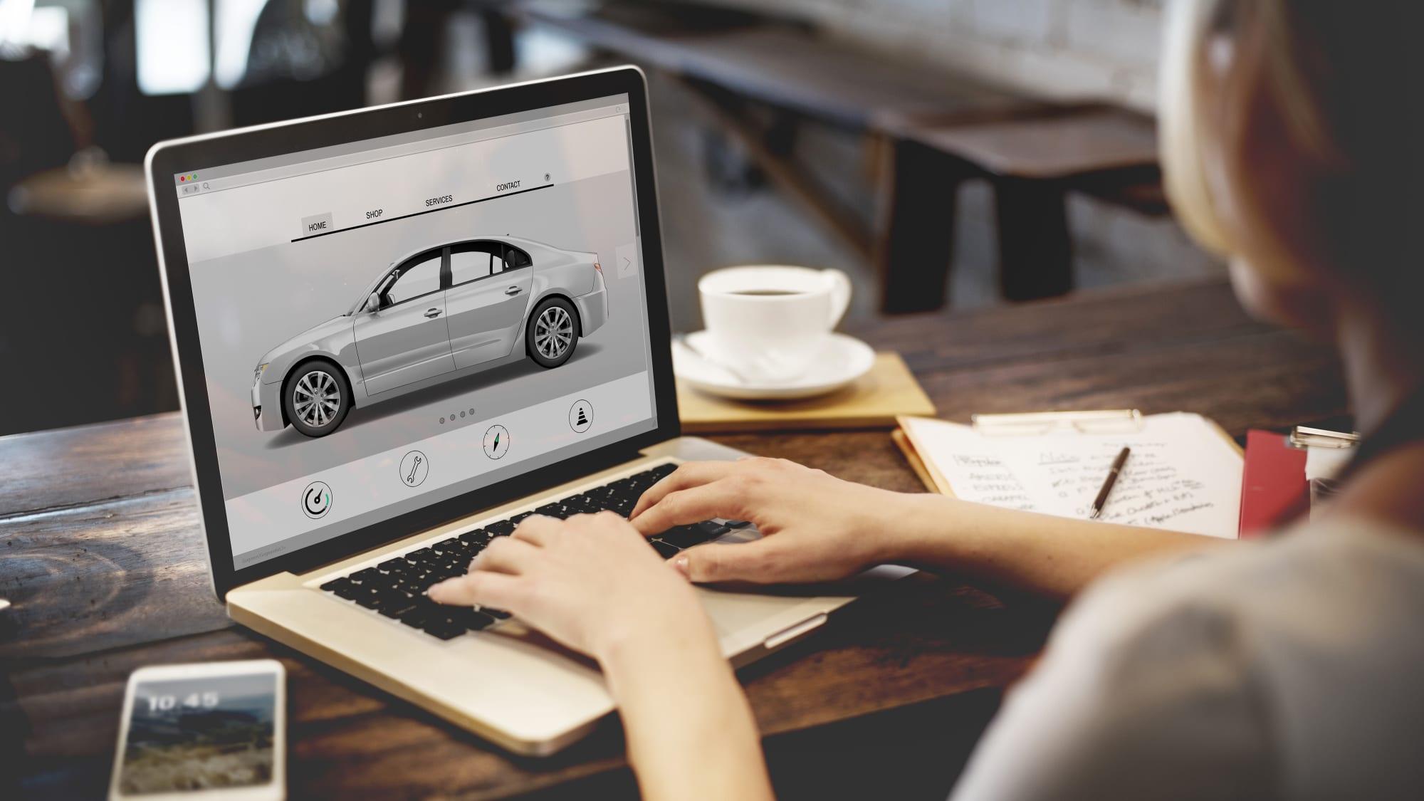 Frau informiert sich am Computer über Fahrzeugdaten zum Autokauf