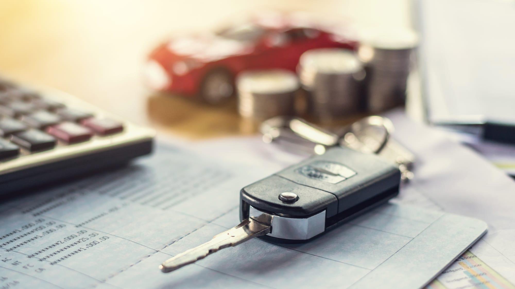 Autoschlüssel mit Geld und Taschenrechner auf dem Tisch