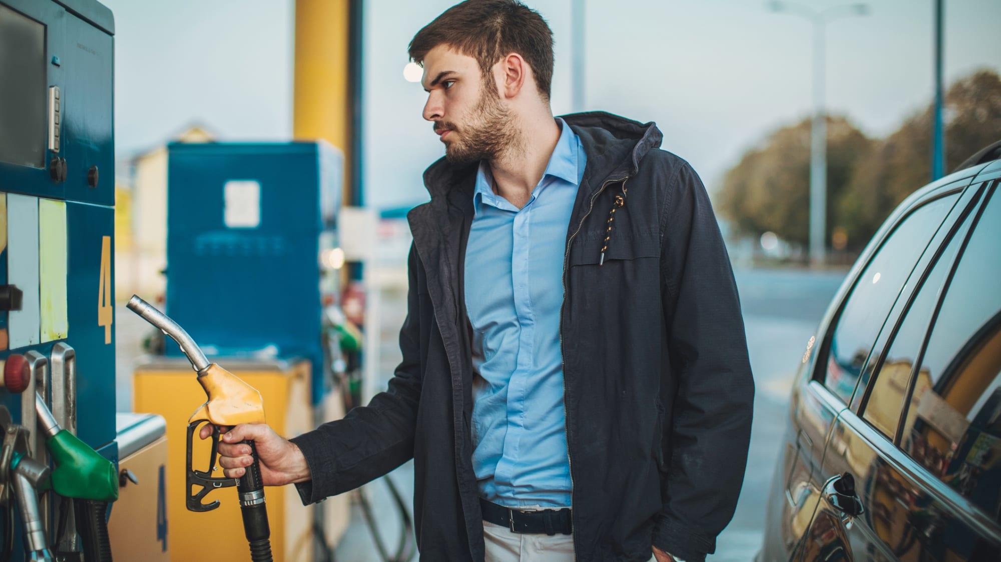 Junger Mann an der Zapfsäule einer Tankstelle