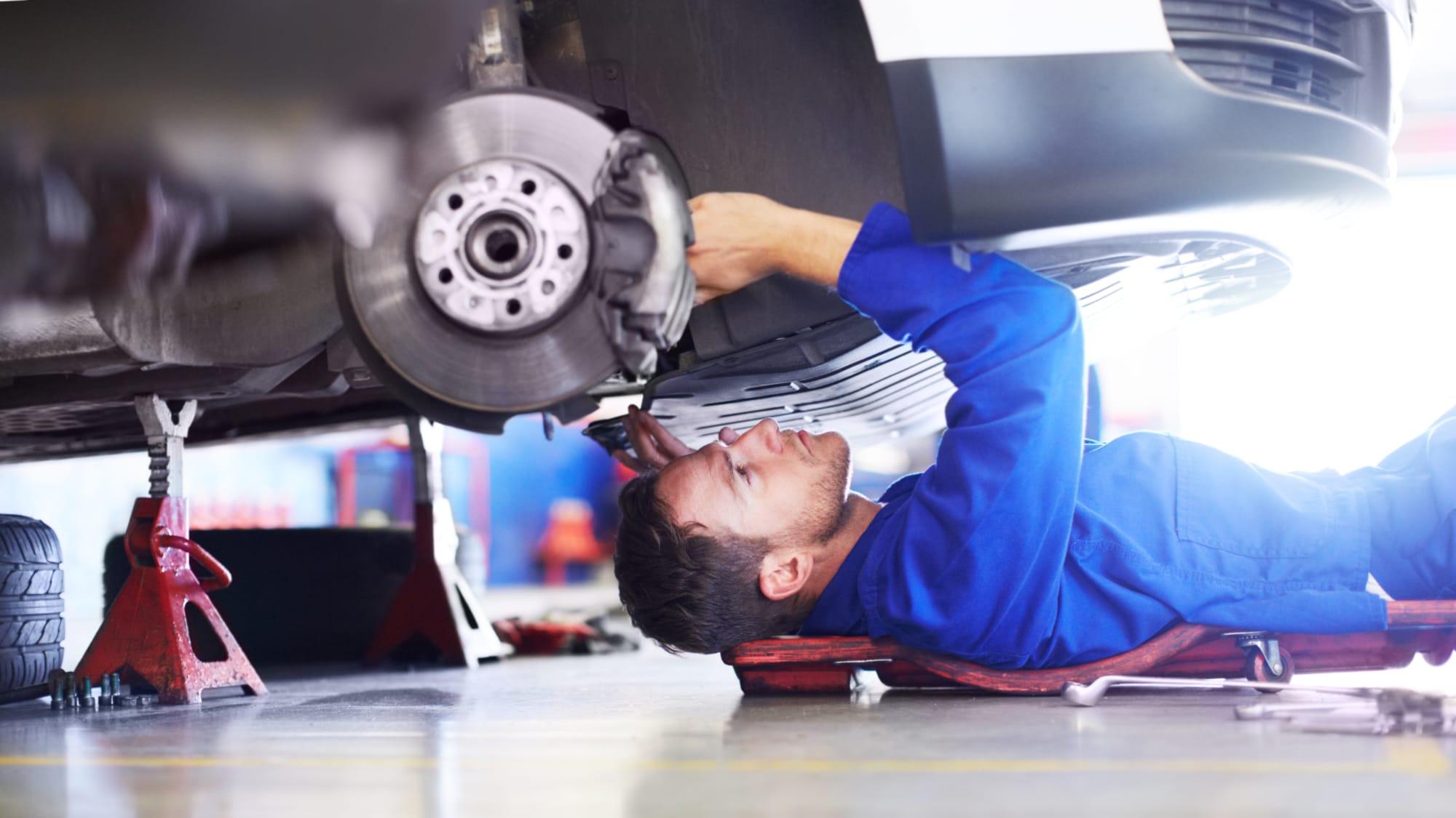 Mechaniker liegt unter einem Auto