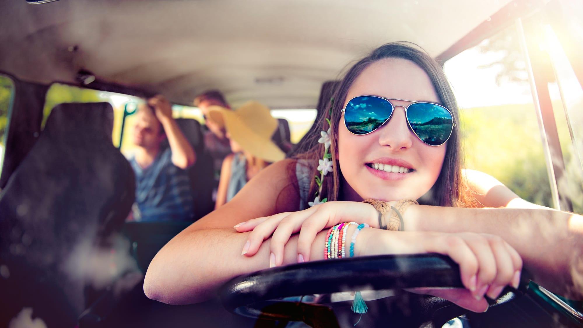 junge Frau am Lenkrad mit Sonnenbrille