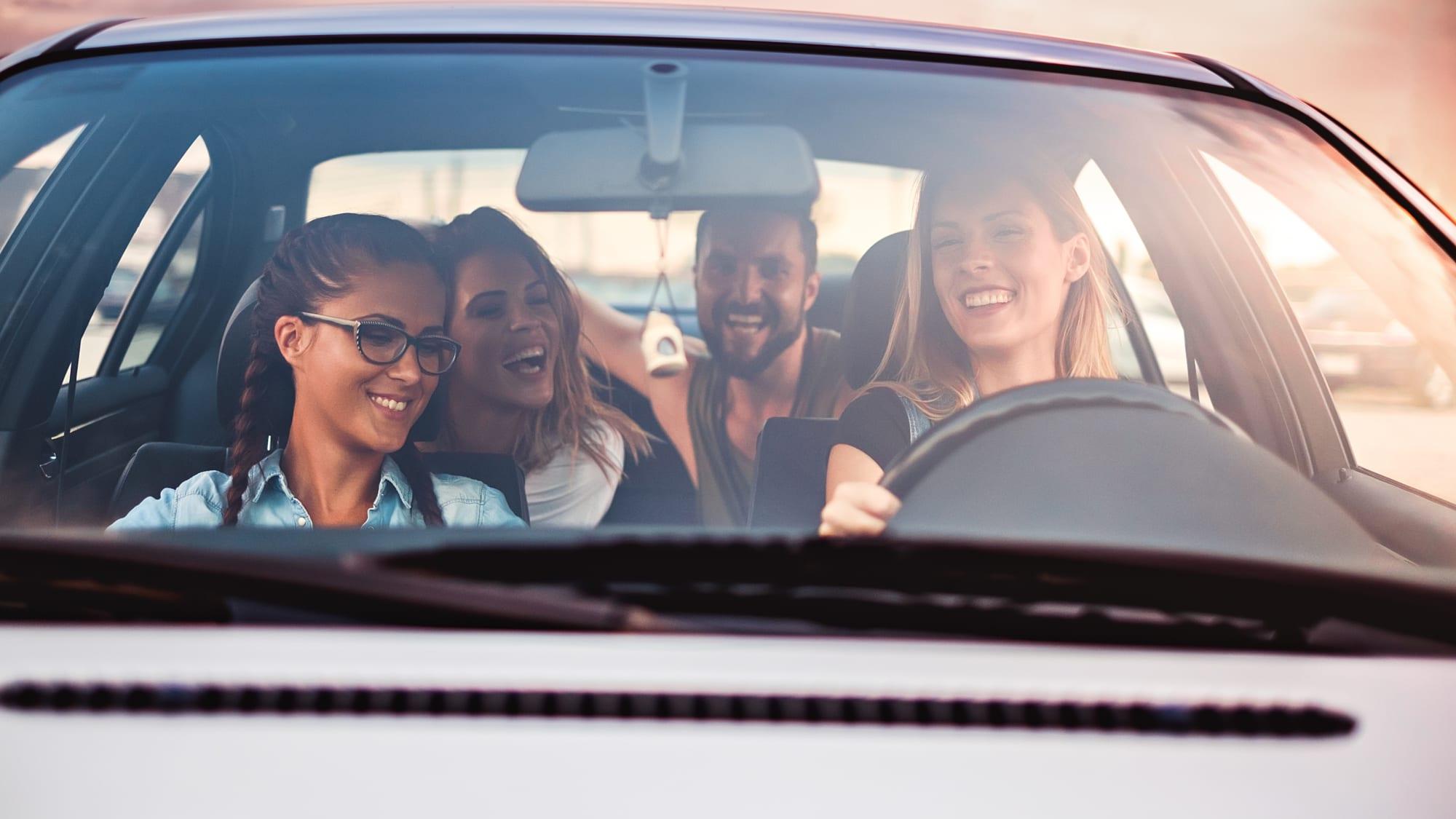 vier Personen fahren in einem Auto