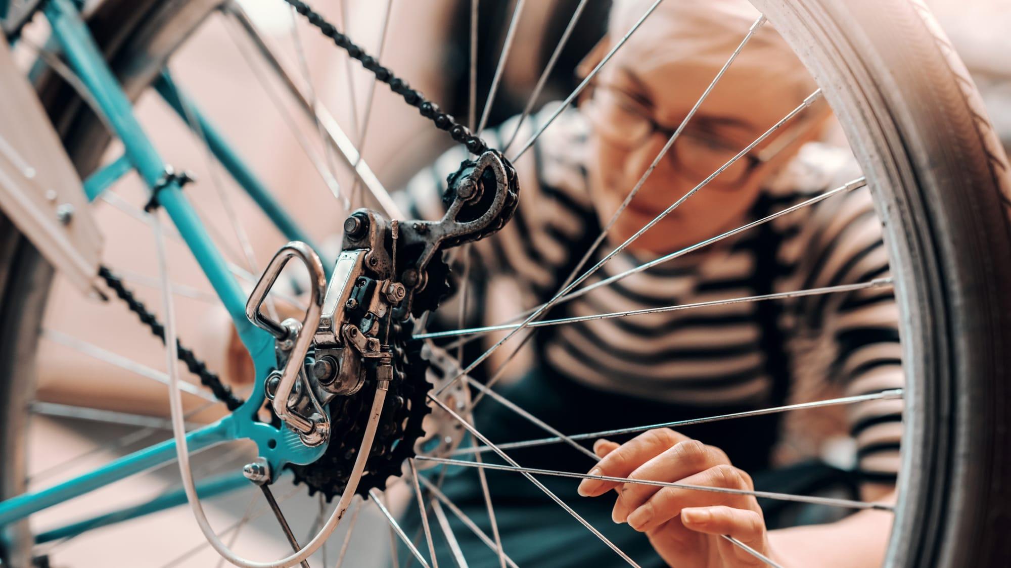 Frau putzt und repariert ihr repariert ihr Fahrrad um es fit für den Frühling zu machen