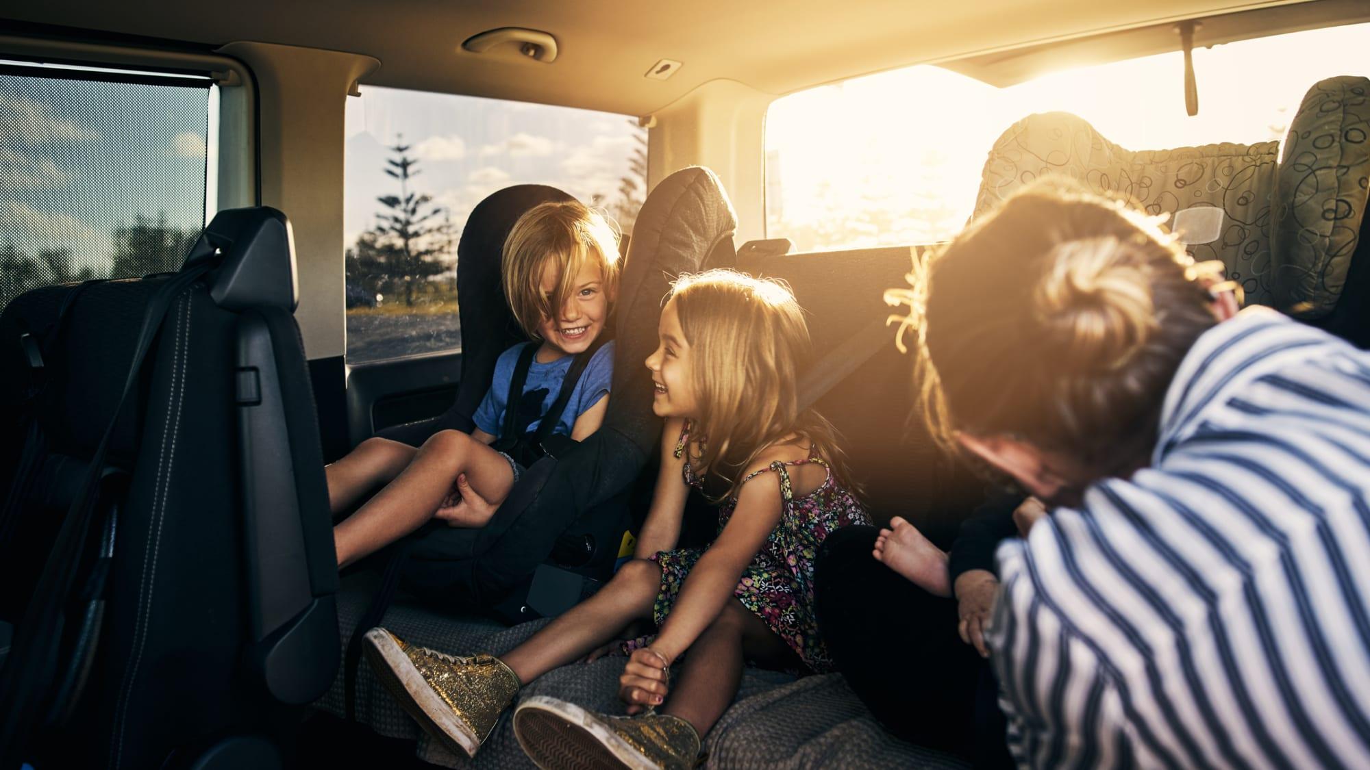 Mutter schnallt drei fröhliche Kinder auf der Rückbank ihres Familienvans fest