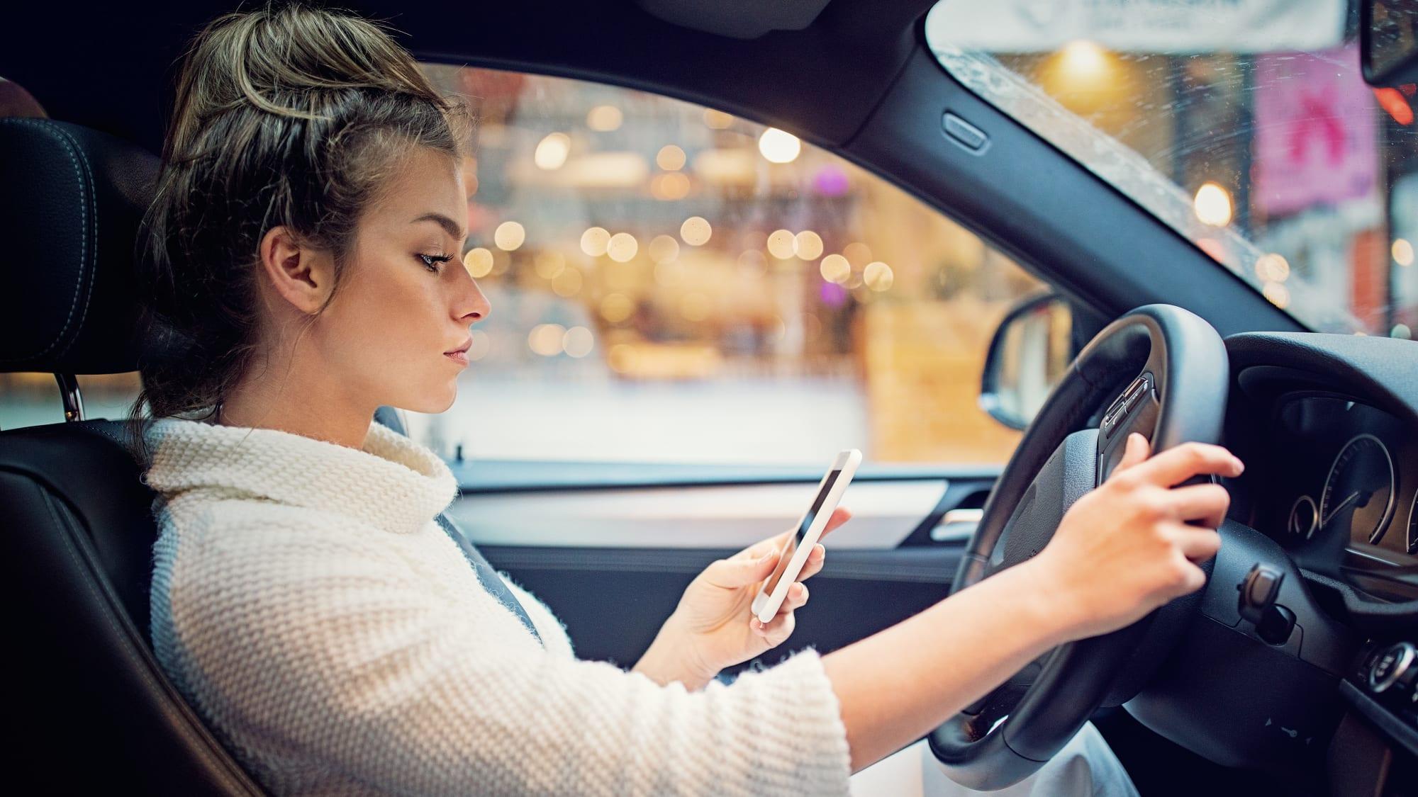Frau schreibt während des Autofahrend auf ihrem Smartphone