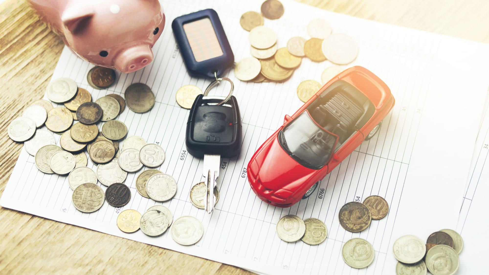 Münzen, Autoschlüssel, Sparschwein und Spielzeugauto auf einem Tisch