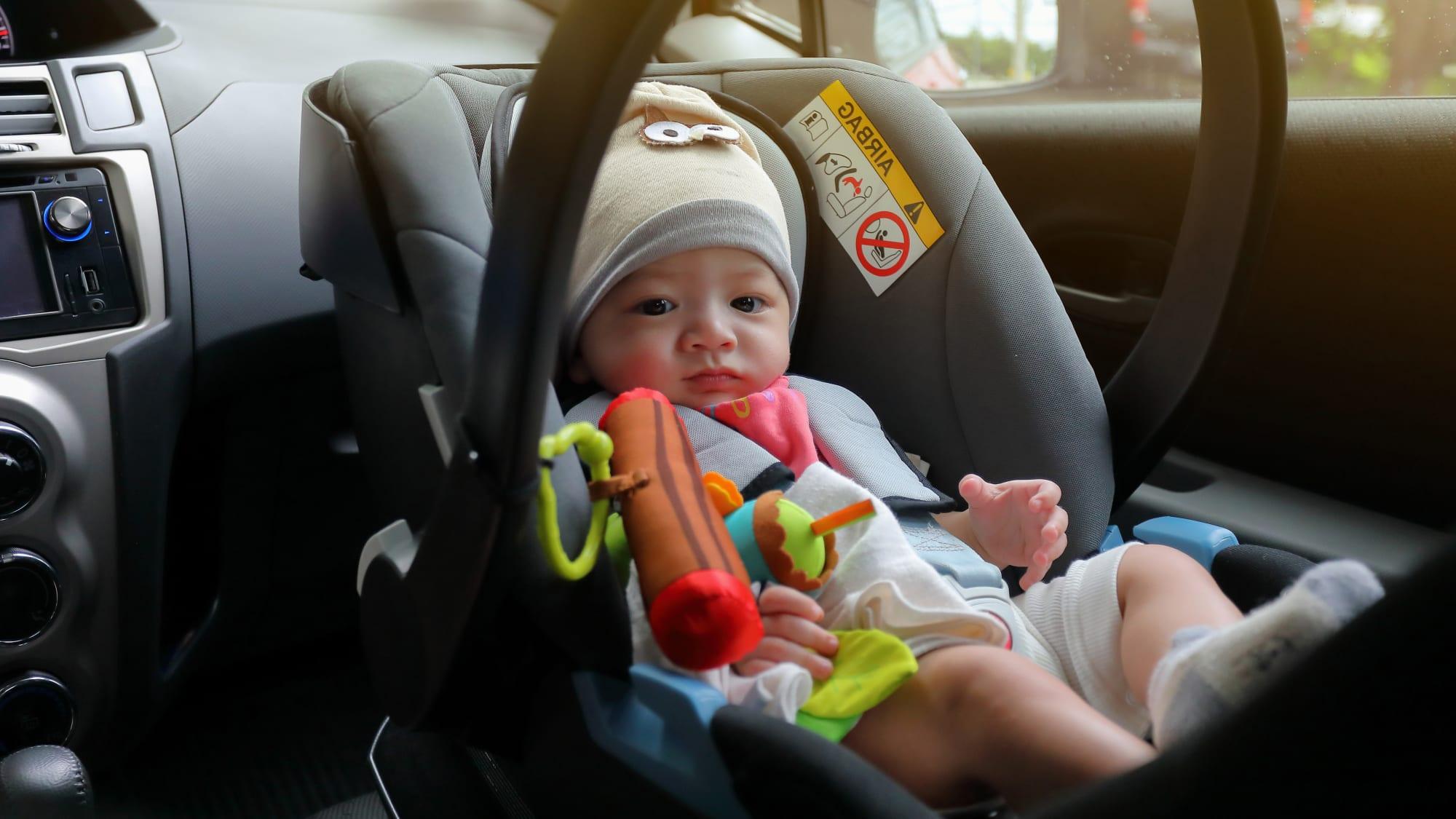 Baby sitzt im Kindersitz auf dem Beifahrersitz im Auto