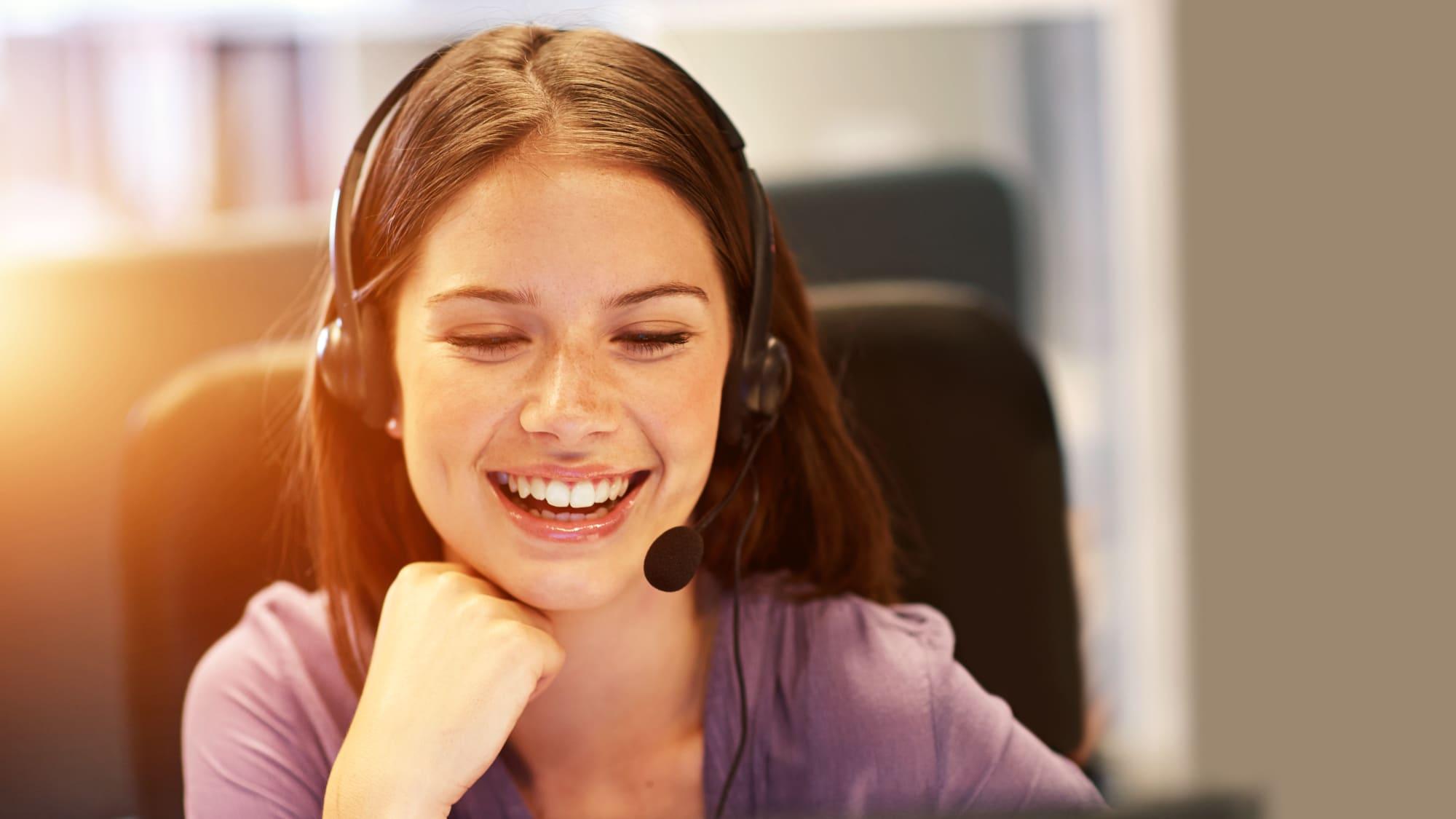 Frau mit Headset blickt auf Bildschirm