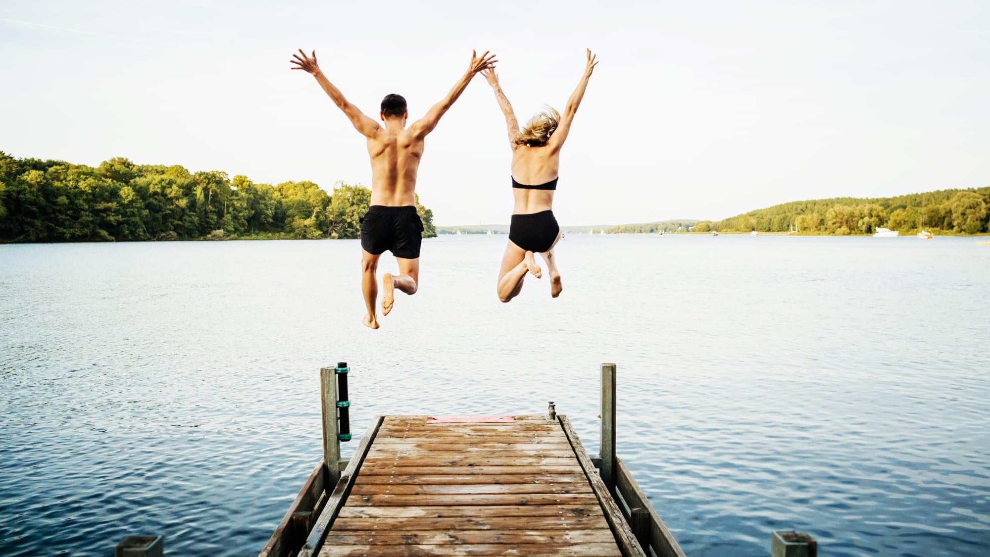 Mann und Frau springen von einem Steg aus in einen See