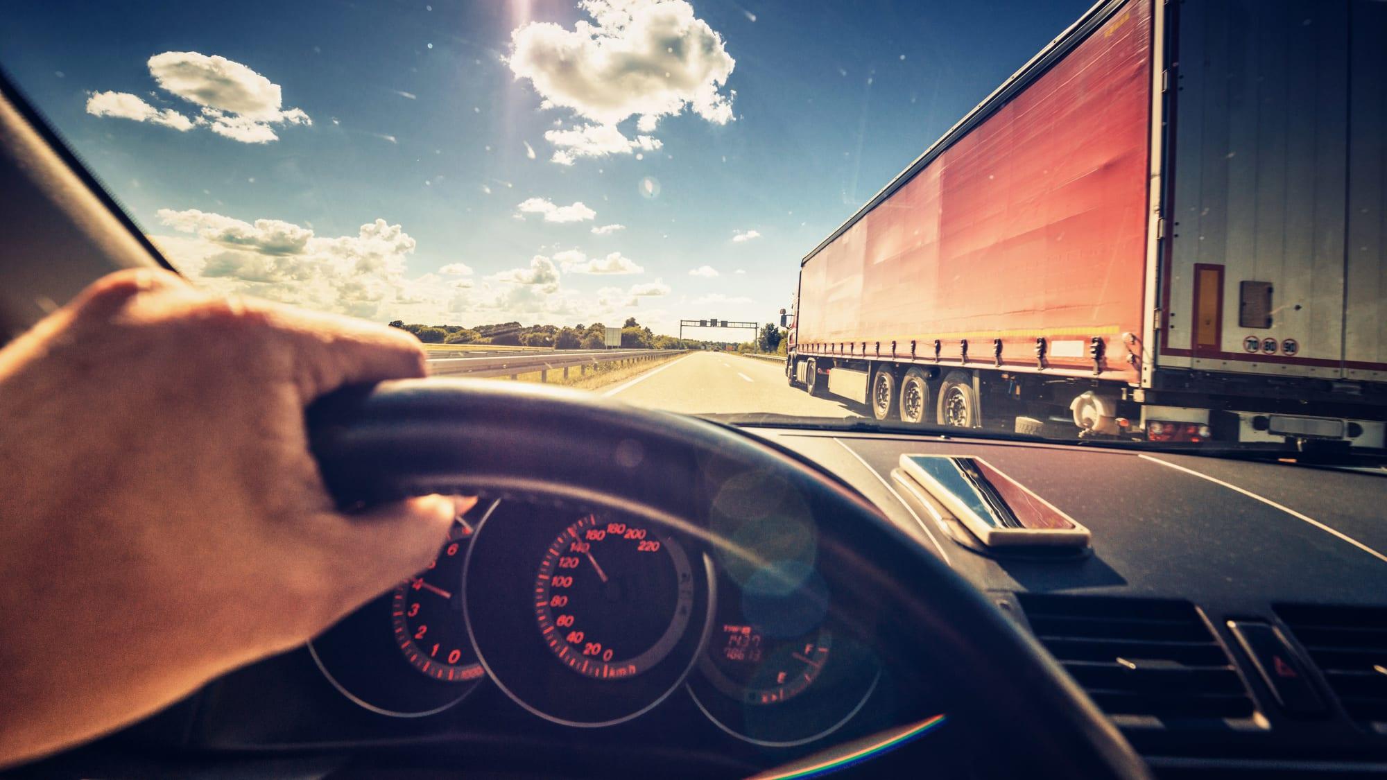 Fahrer auf Autobahn fährt neben einem LKW