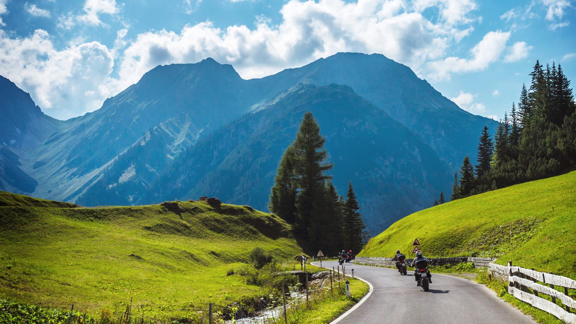 Motorradfahrer auf einer Straße mit Bergkulisse