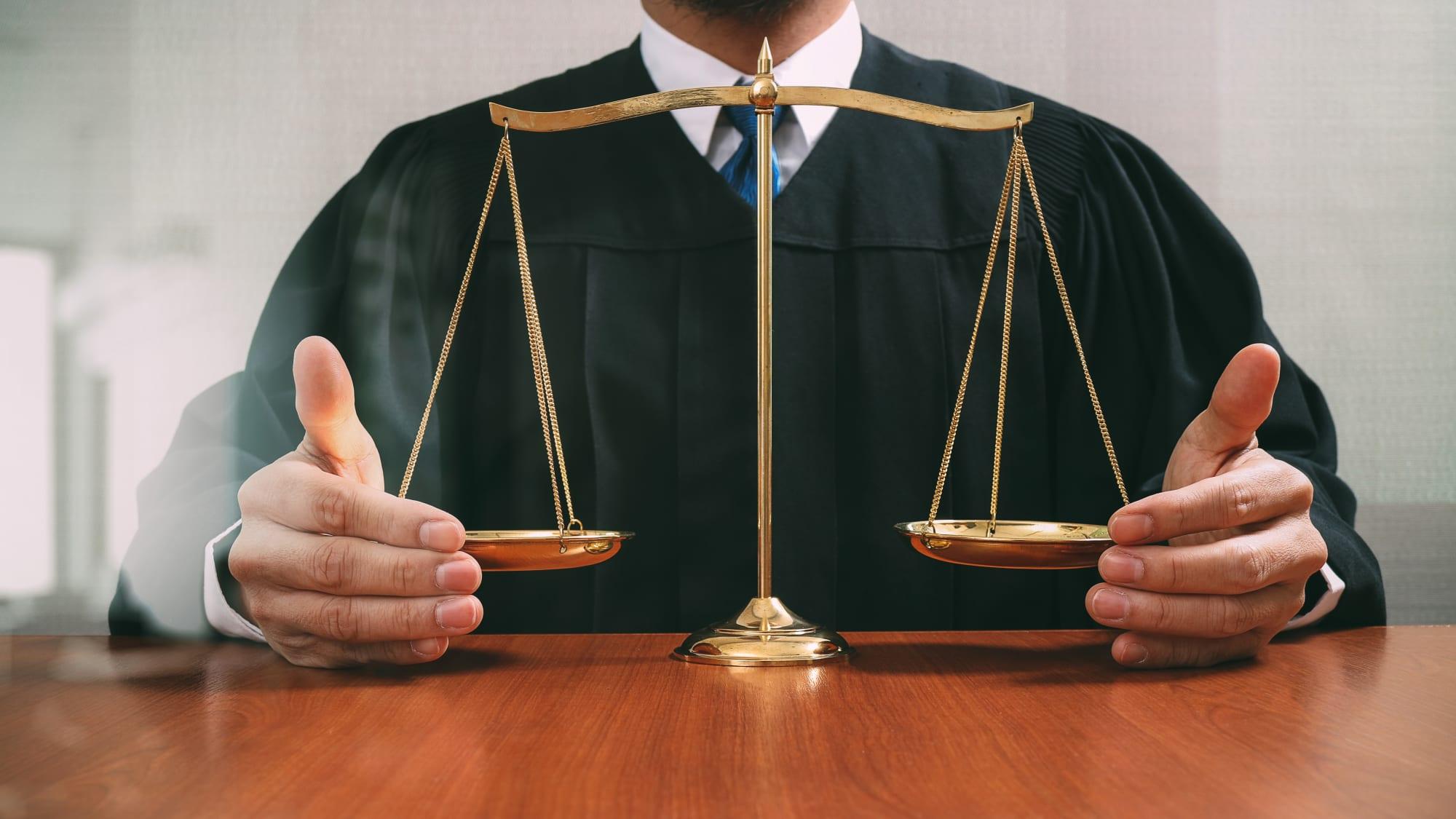 Richter mit Händen an der Waagschale