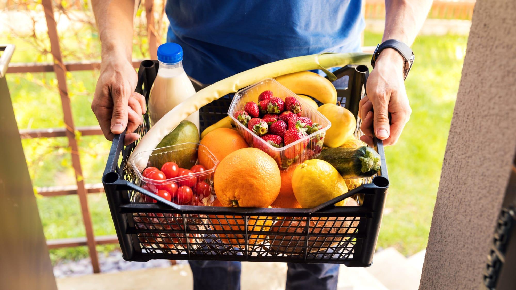 Mann hält Kiste mit Obst in der Hand
