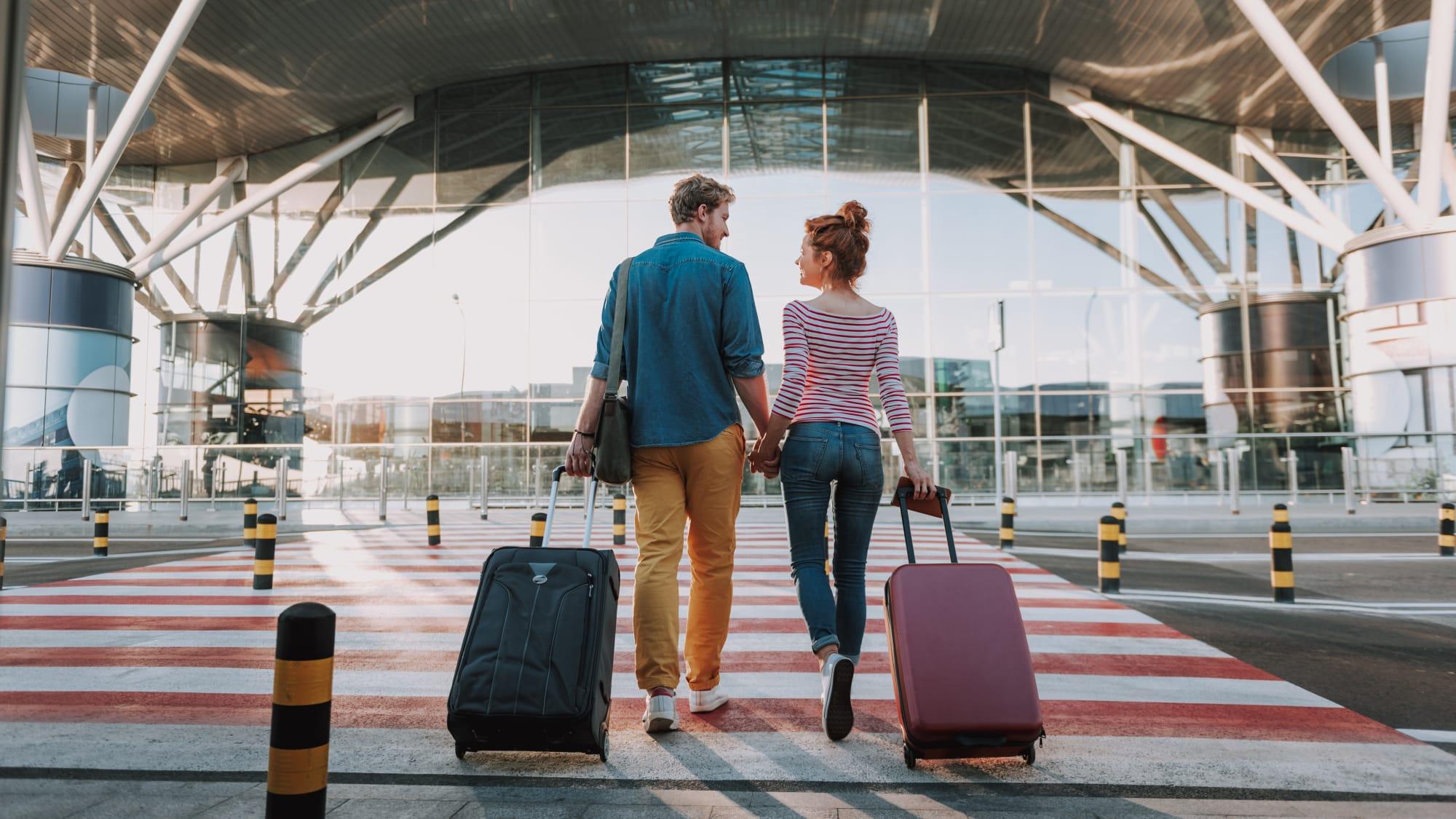 Paar geht mit ihren Koffern in einen Flughafen