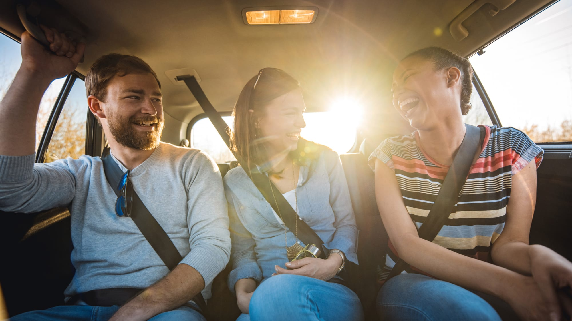 Drei junge Menschen auf der Rueckbank in einem Auto