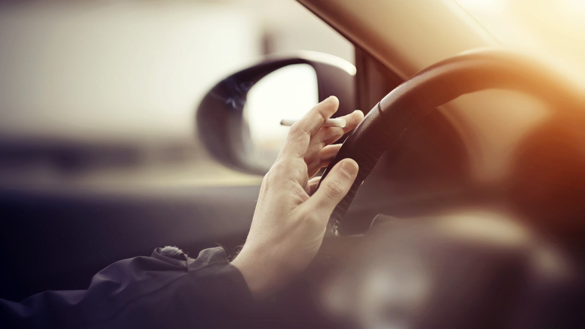 Mann mit Zigarette in der Hand fährt Auto