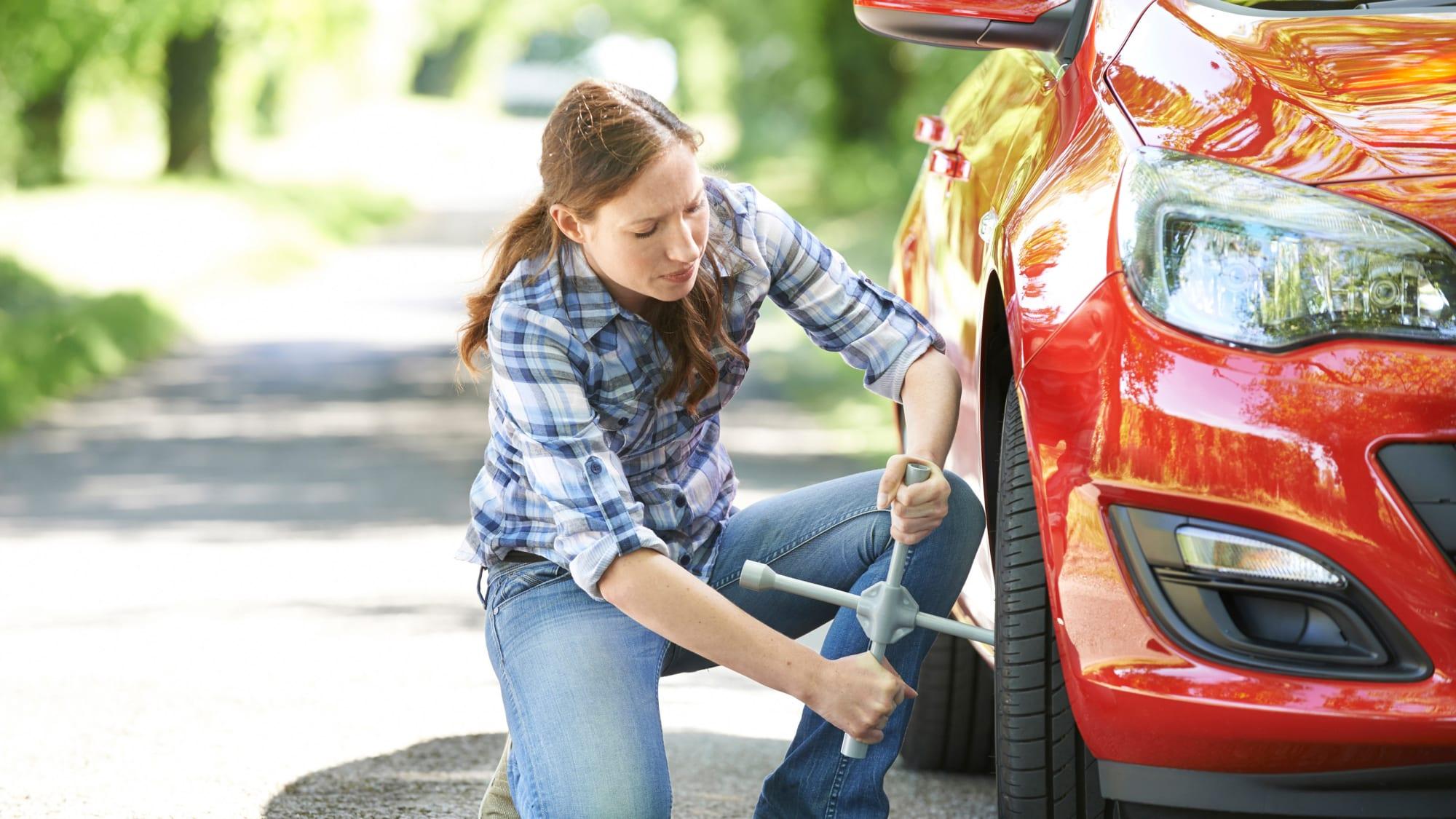 Frau wechselt Reifen an einem roten Auto