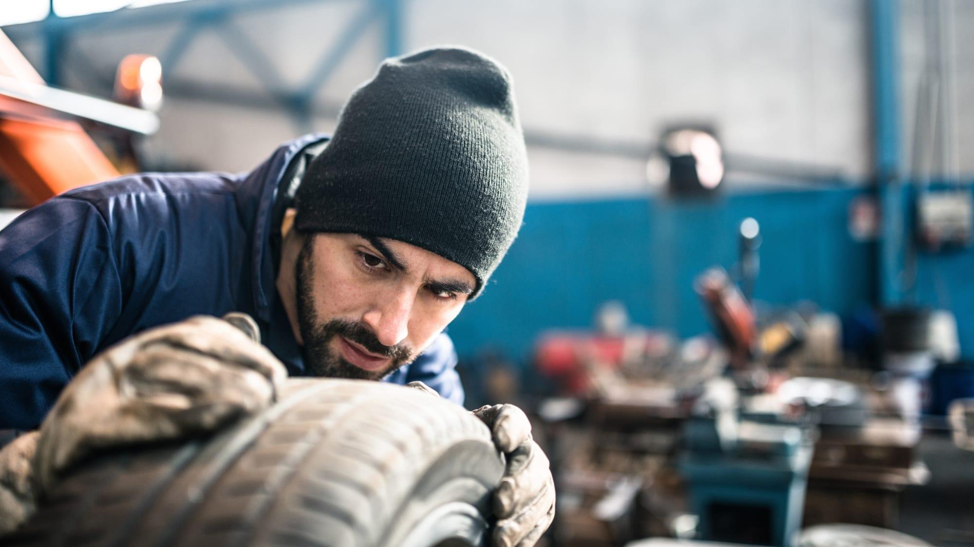 Automechaniker betrachtet das Profil eines Reifens