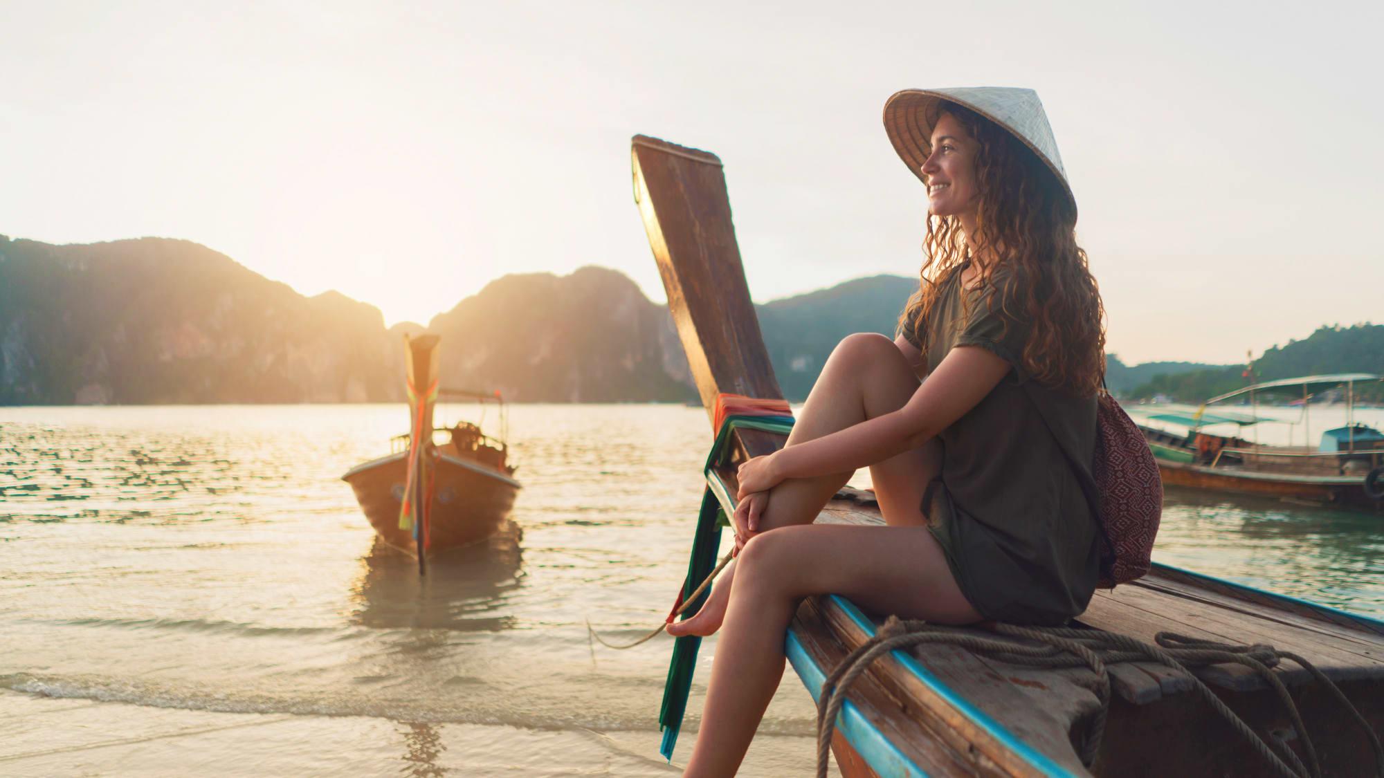 Junge Frau sitzt auf einem Holzboot am Strand