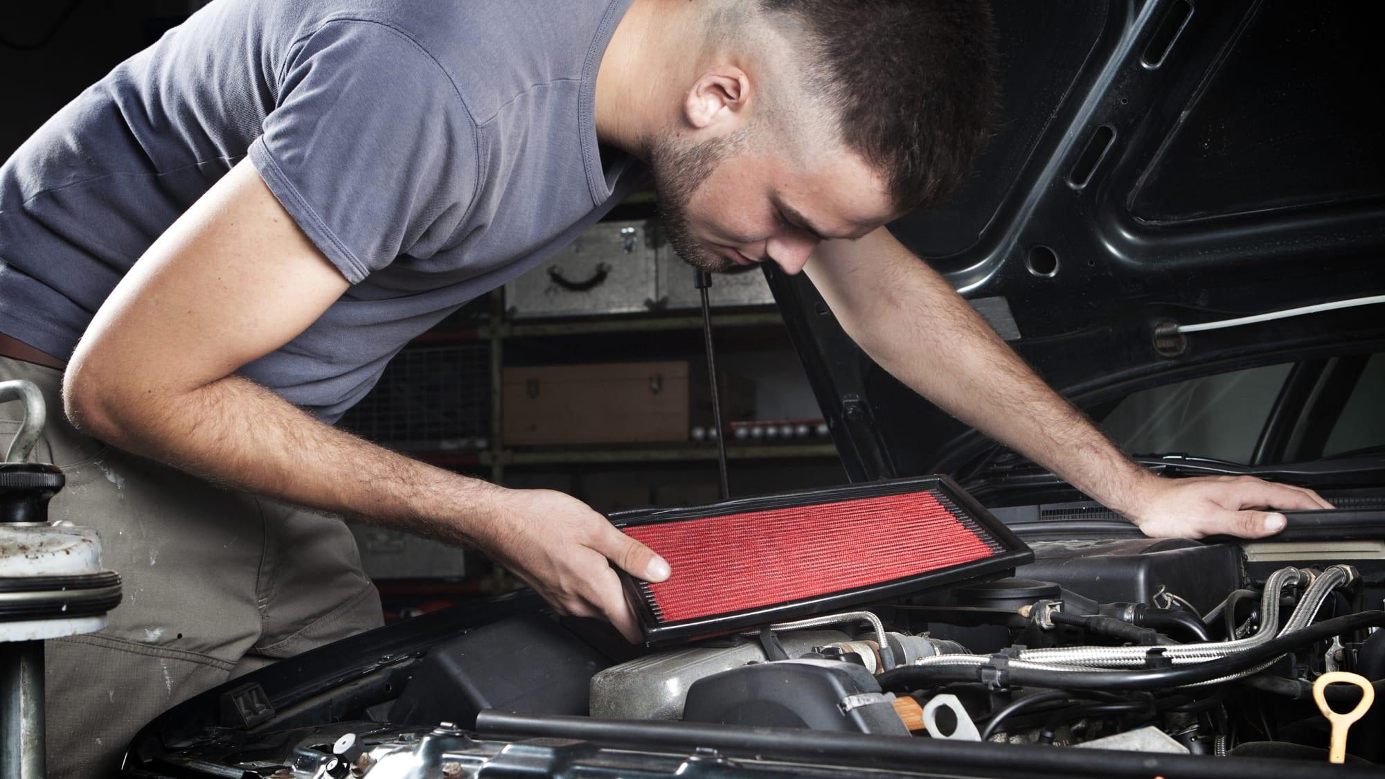 Mechaniker beugt sich über einen Motor und hat einen neuen Luftfilter in der Hand.