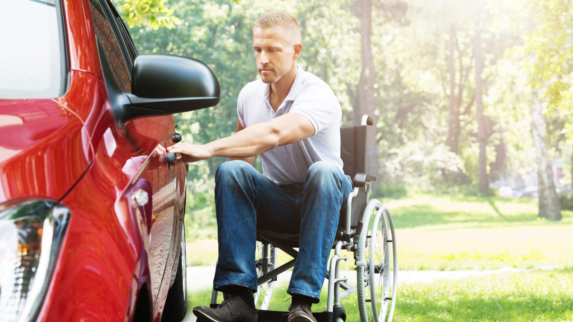 Männlicher Rollstuhlfahrer öffnet Autotüre