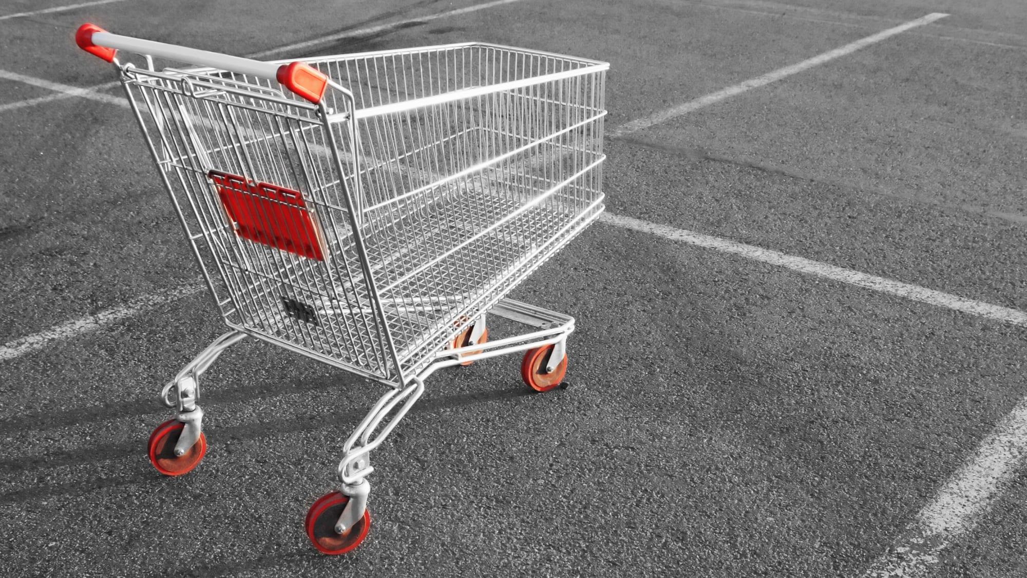 Leerer Einkaufswagen steht auf einem Parkplatz