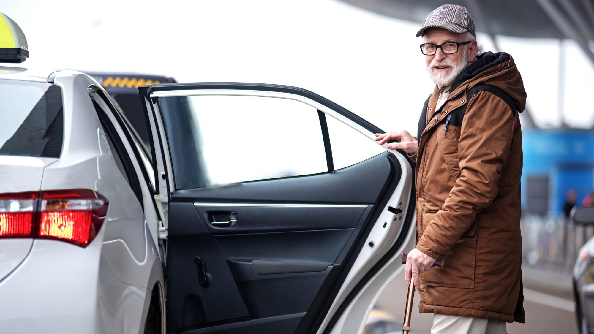 Älterer Herr steigt in Taxi