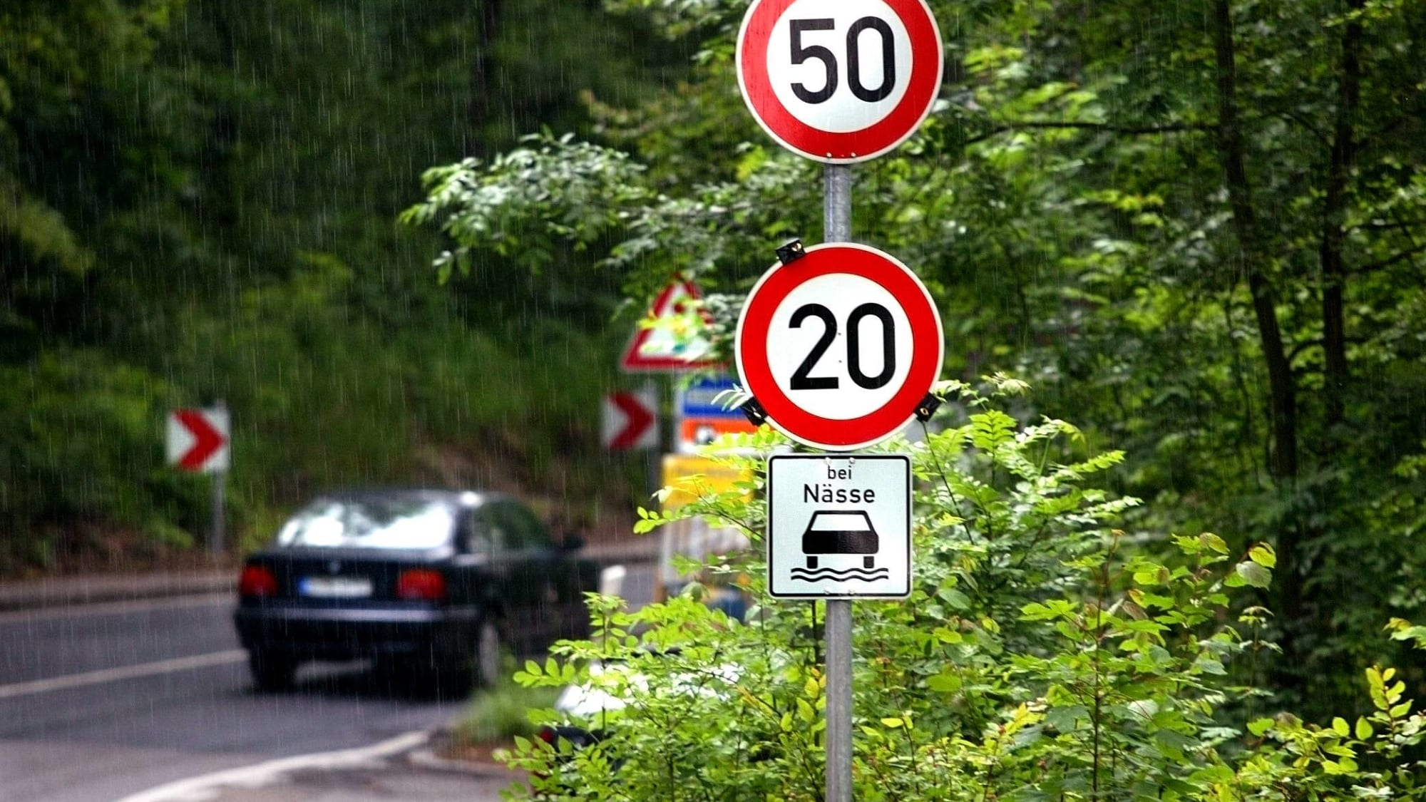 Ein Auto fährt bei Nässe um eine Kurve vorbei an einem Tempolimit-Schild