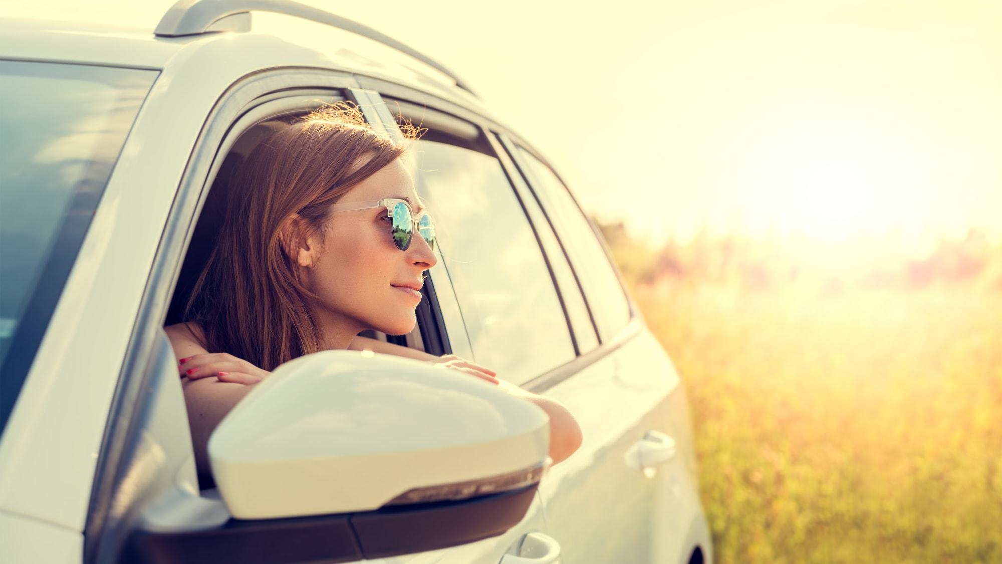 Frau mit Sonnenbrille schaut aus einem Auto in die Sonne