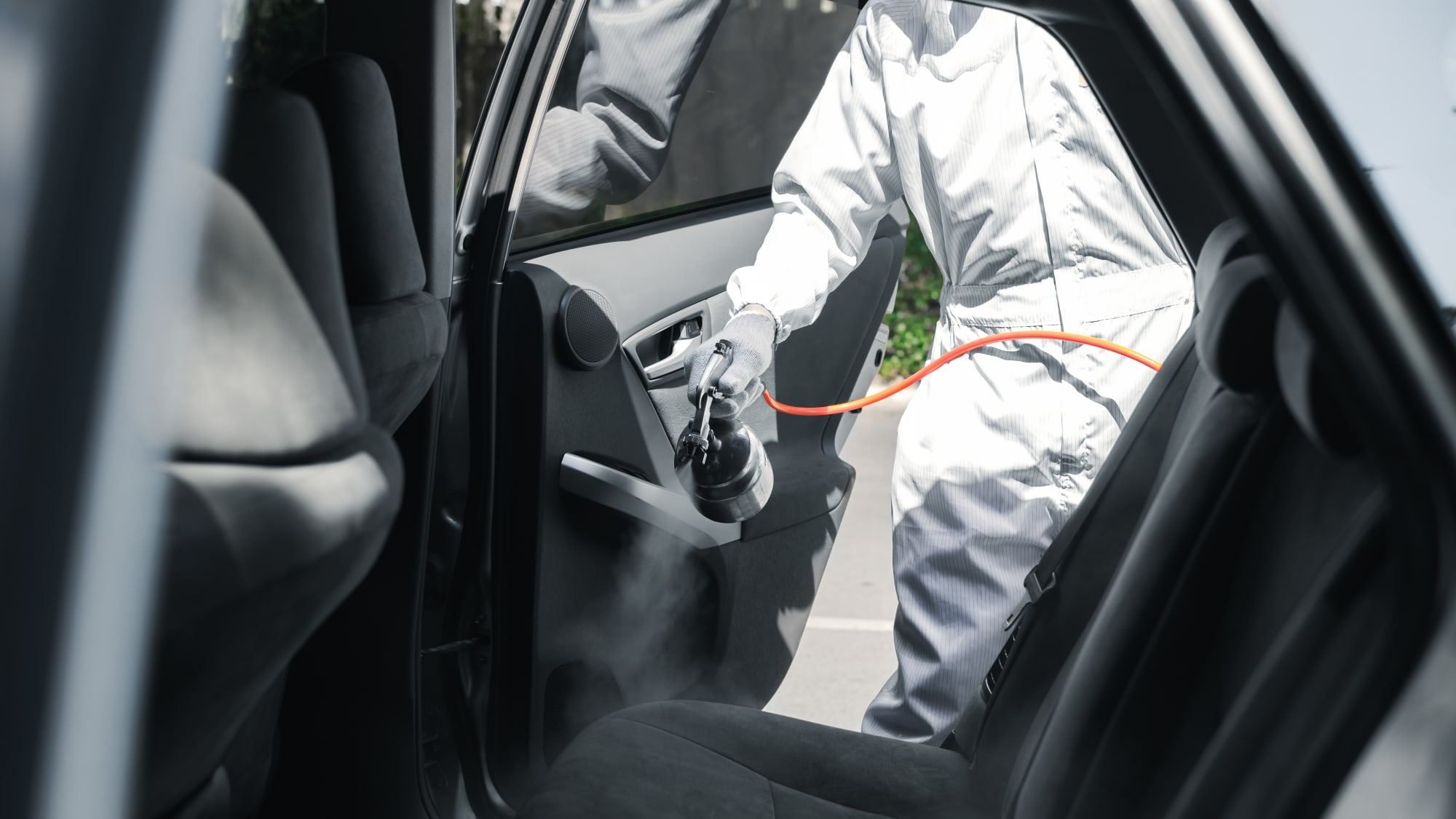 Person in Schutzkleidung desinfiziert die Rückbank eines Autos