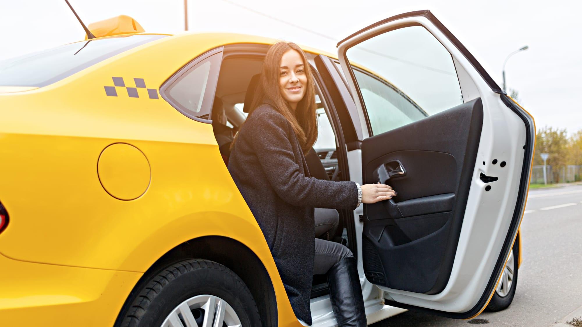 Damen in schwarzem Mantel öffnet die Türe des Taxis beim Aussteigen