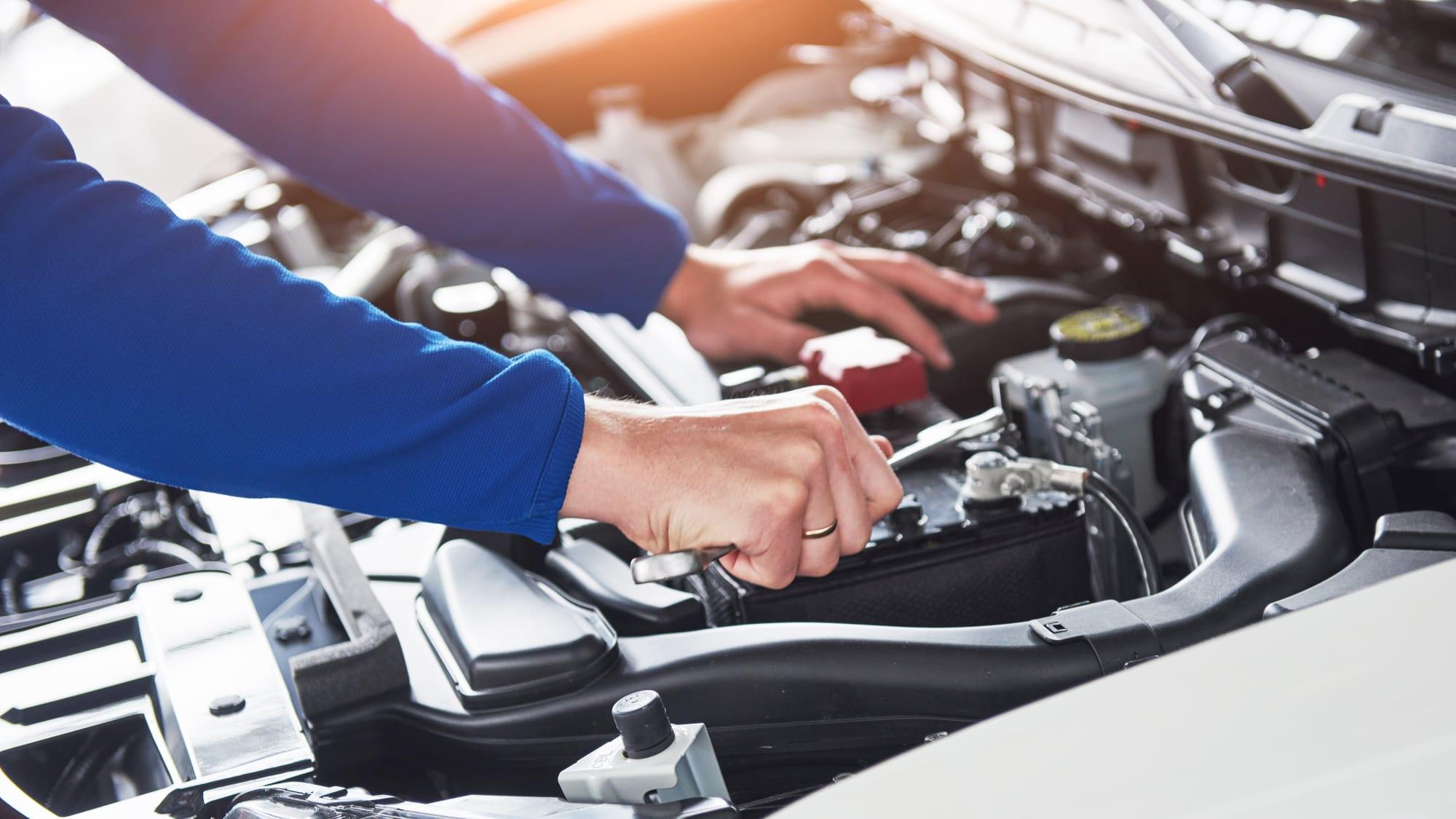 Mechankiker-Hände mit Werkzeug arbeiten an einem Motor