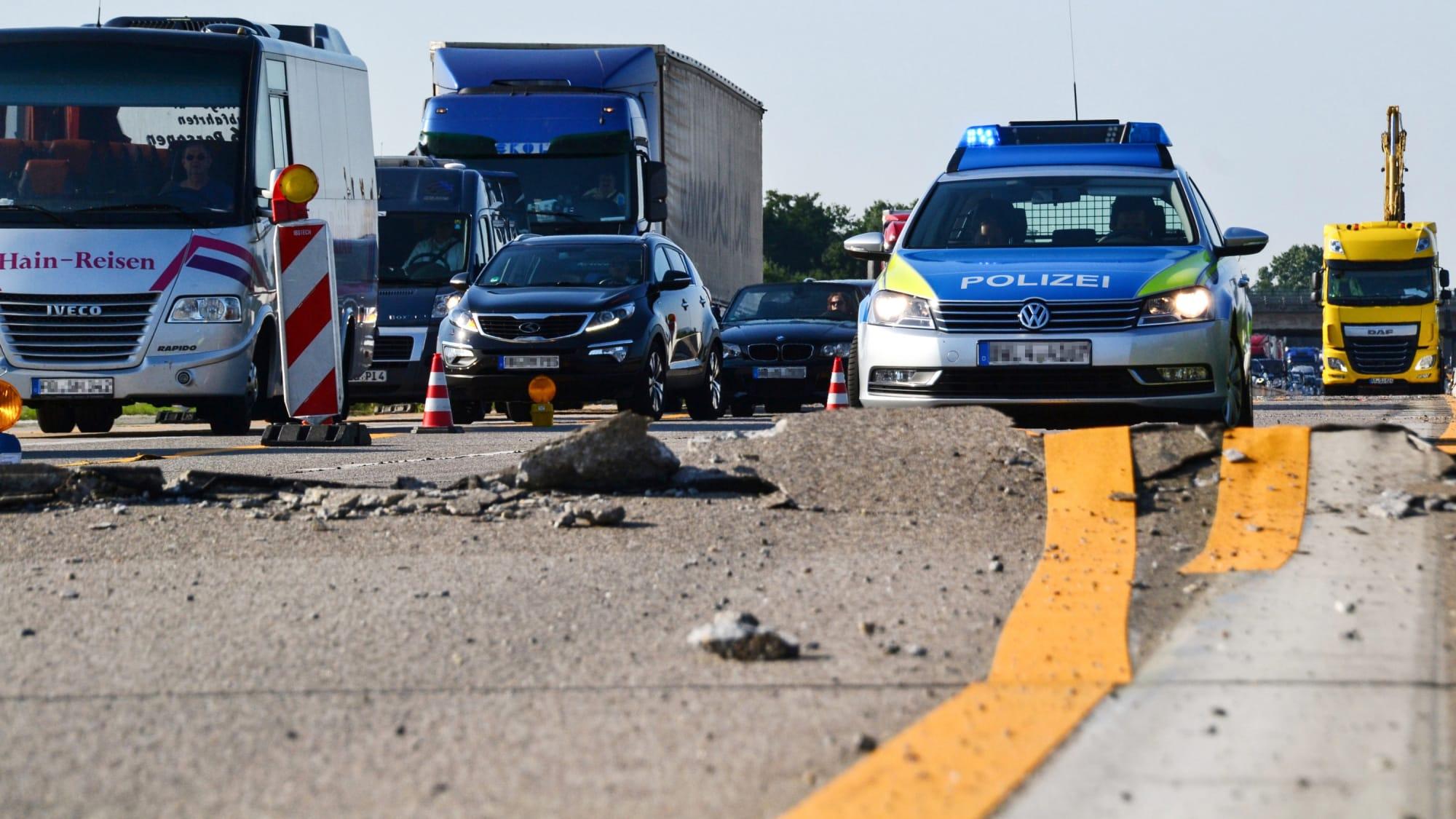 Ein Polizeiauto steht vor einer aufgerissenen Strasse