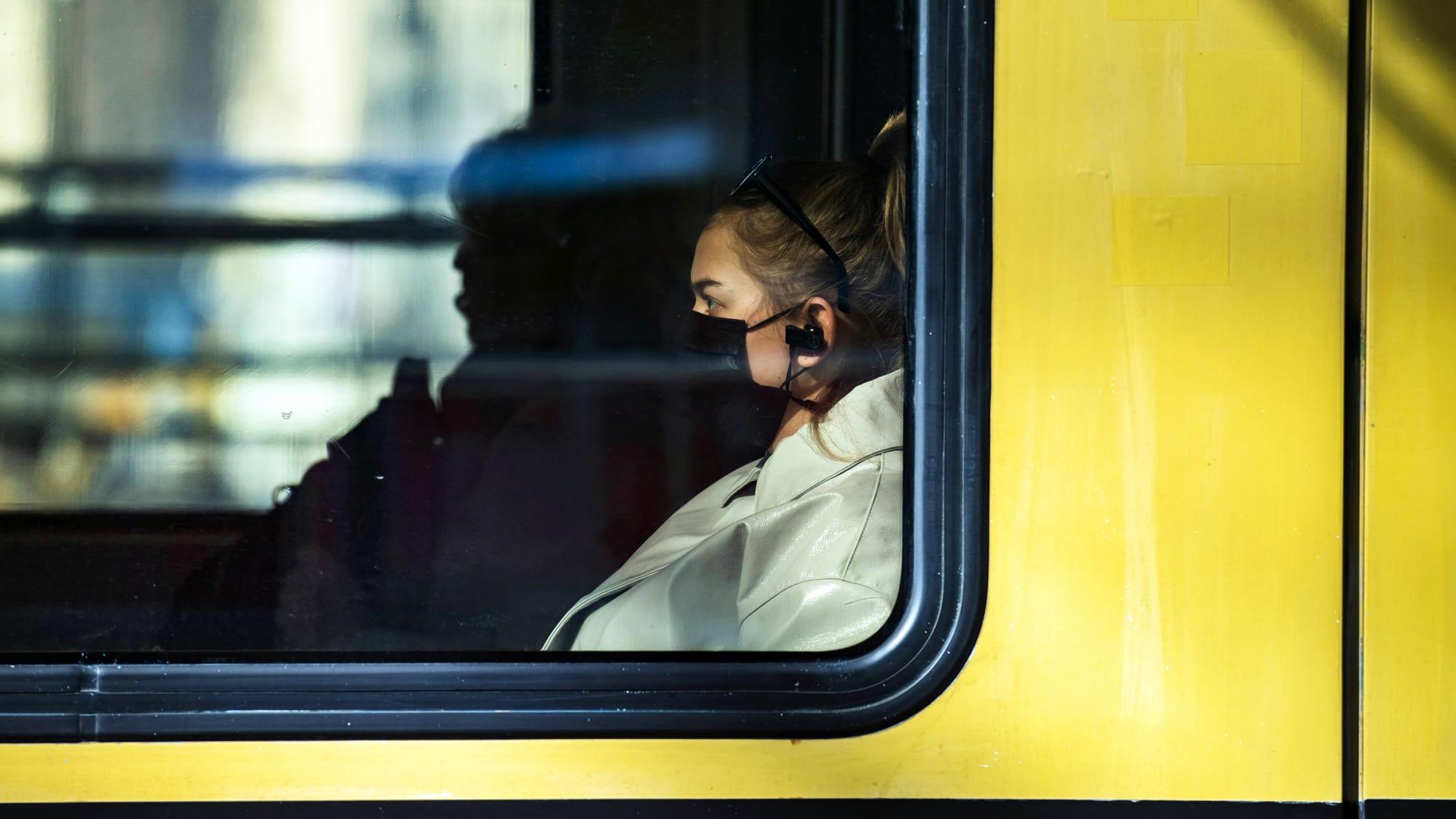 Frau fährt mit Mundschutz im Zug