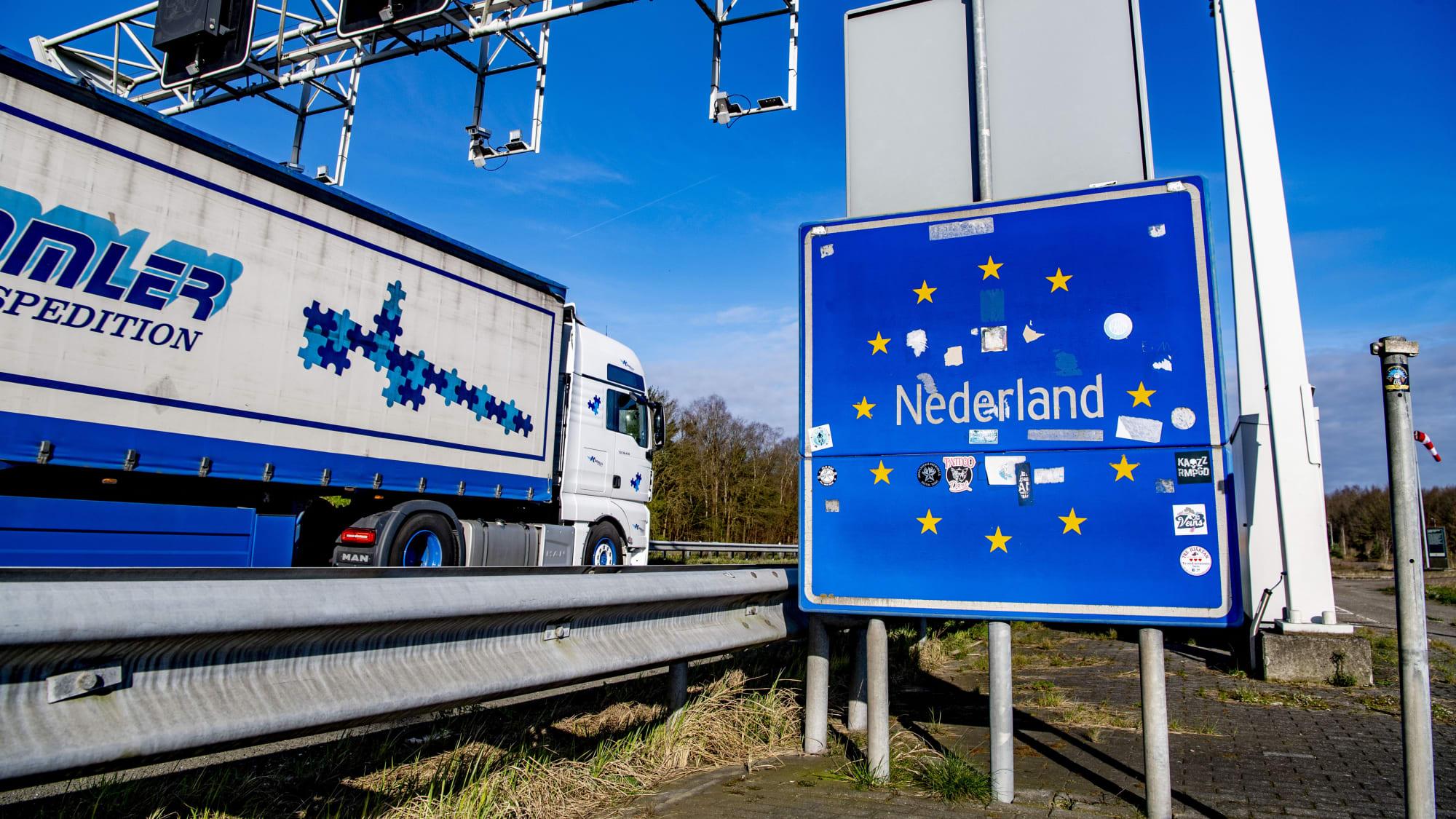 Ein LKW fährt auf der Autobahn am Grenzschild der Niederlande vorbei