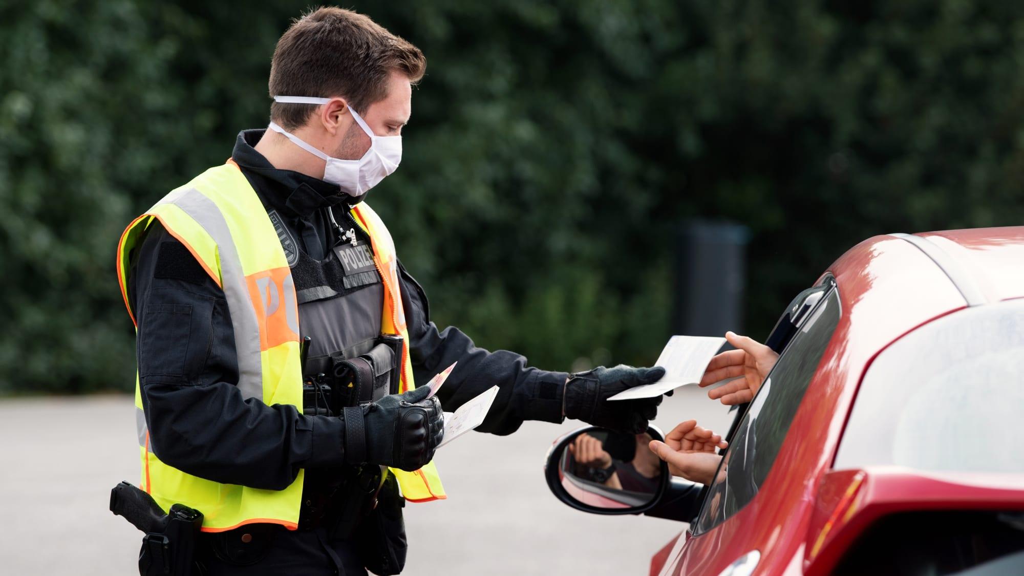 Polizist kontrolliert Papiere eines Autofahrers
