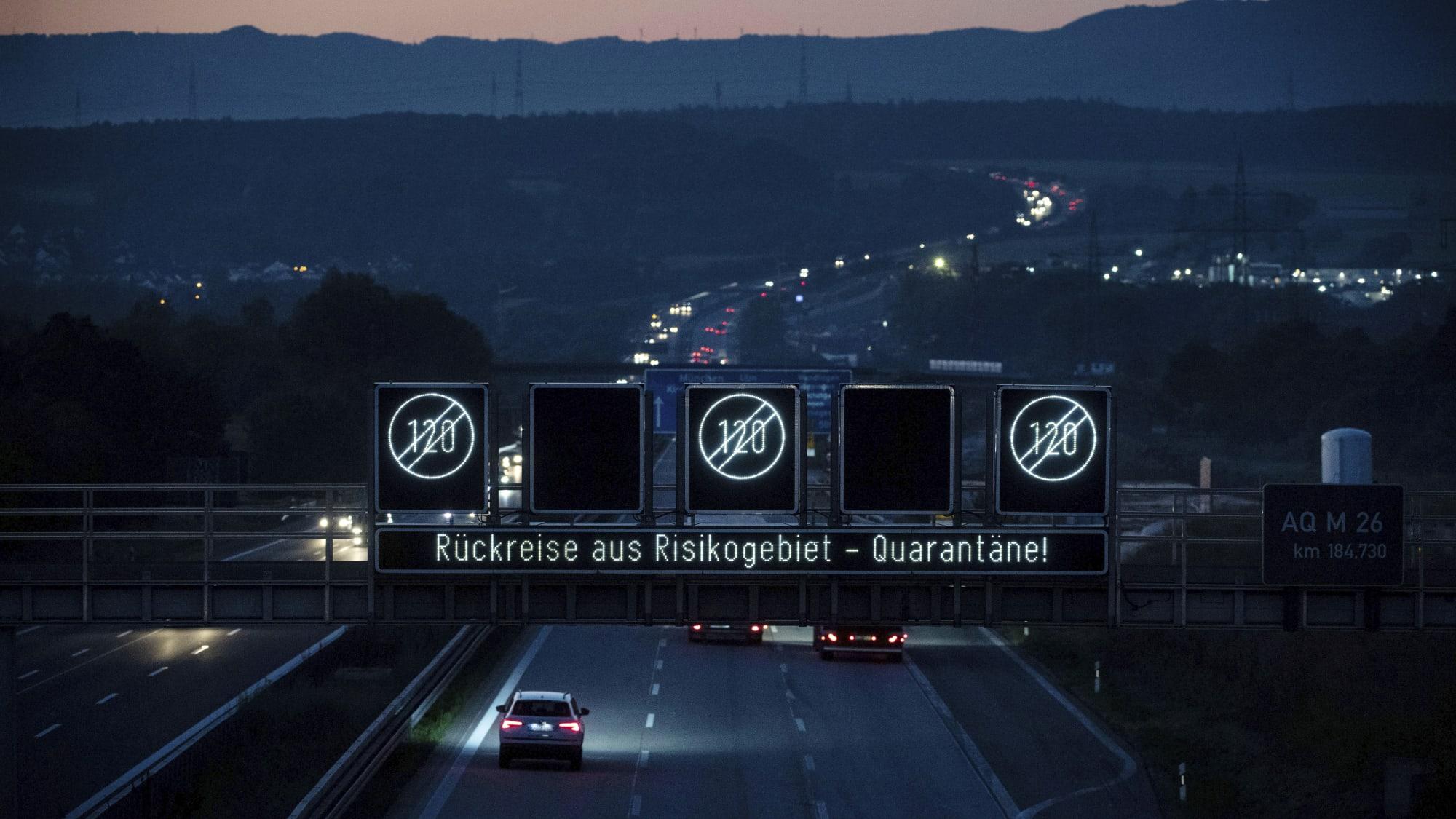 """Autobahn mit Hinweis-Leuchttafel: """"Rückreise aus Risikogebiet - Quarantäne"""", über der Fahrbahn, in der Dämmerung."""