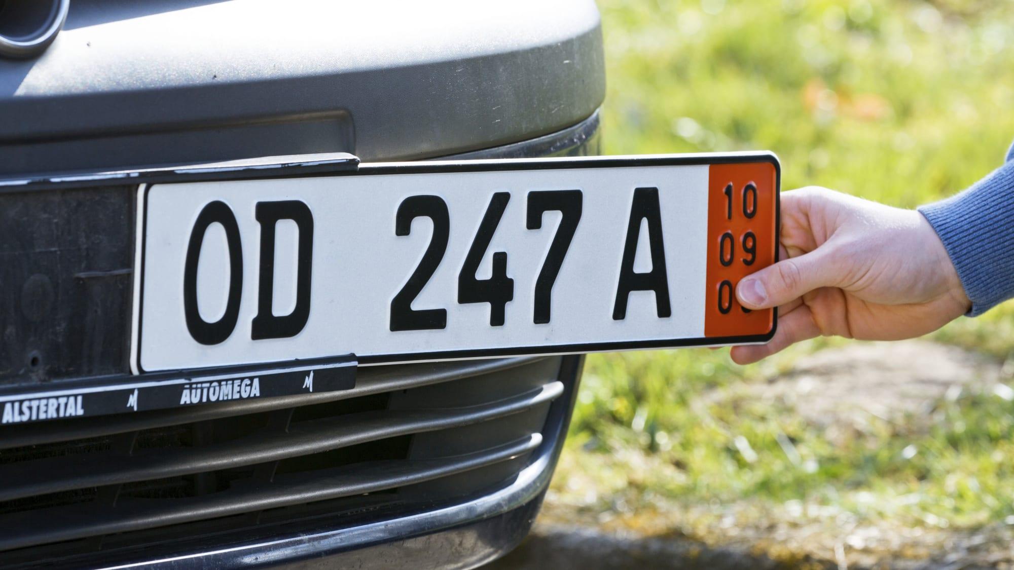 Ein Mann befestigt an der Prägestelle in Bad Oldesloe ein Ausfuhrkennzeichen an einem Auto