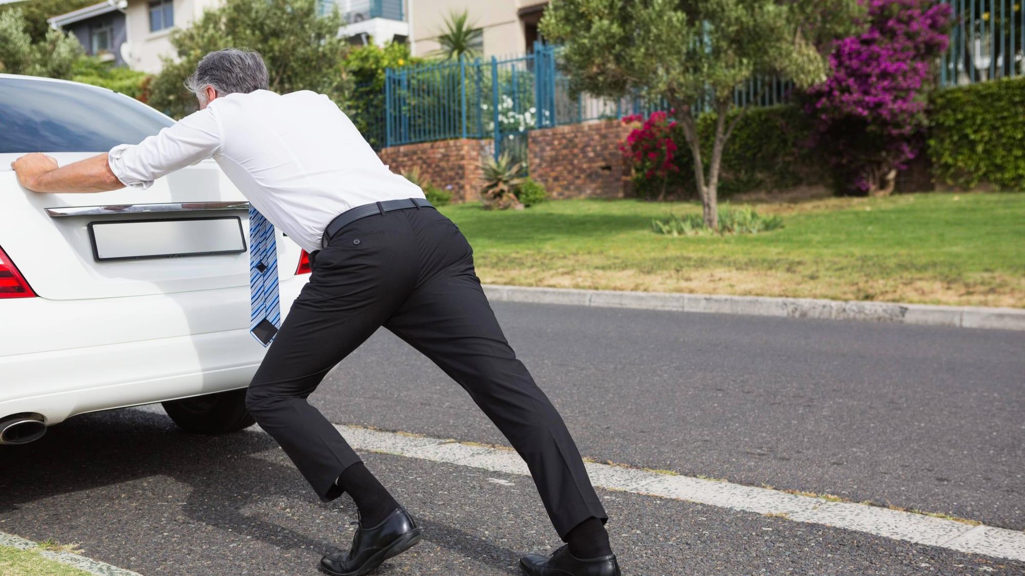 Mann schiebt ein Auto auf der Strasse an