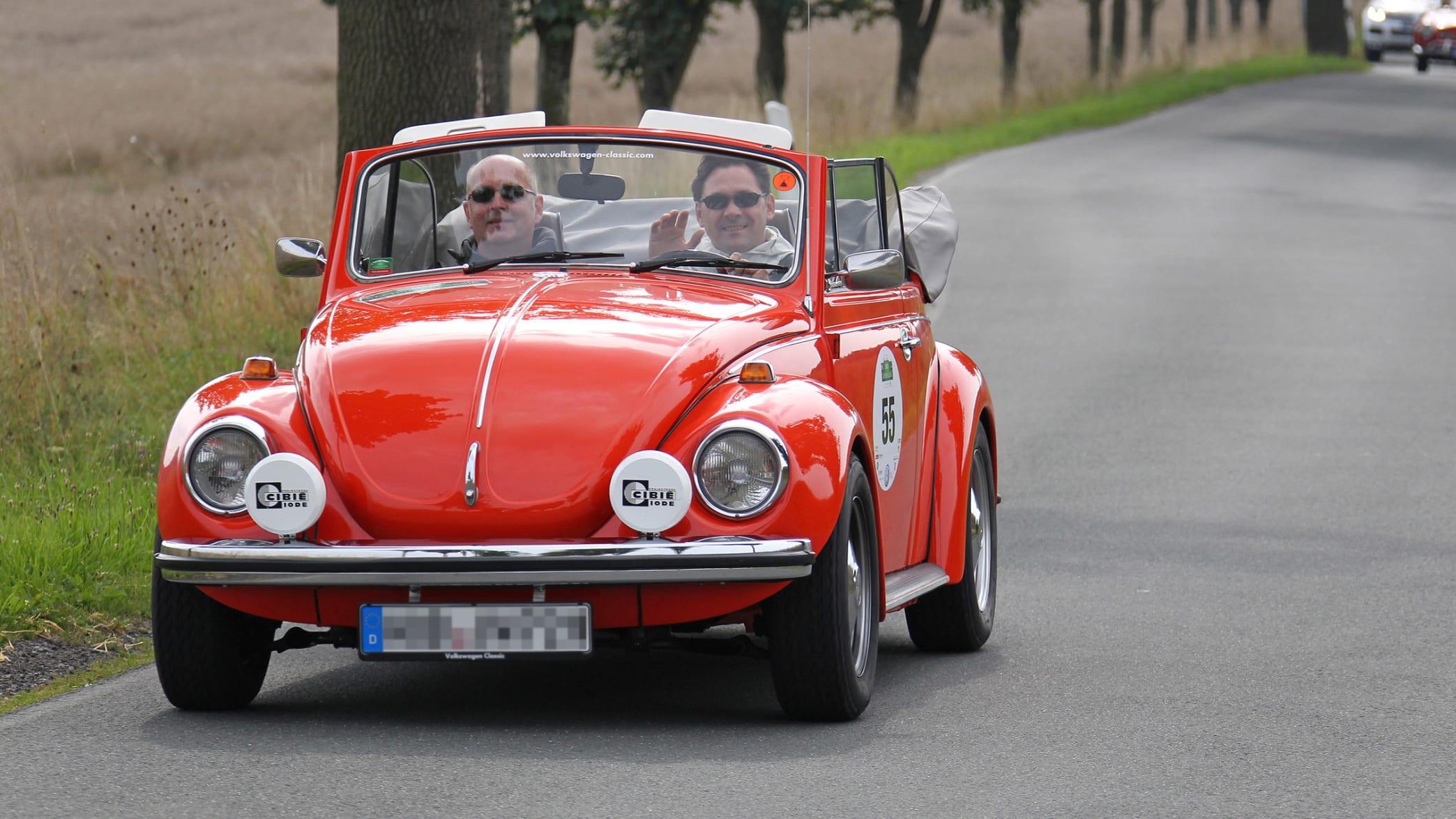 Roter VW Käfer fährt auf einer Straße